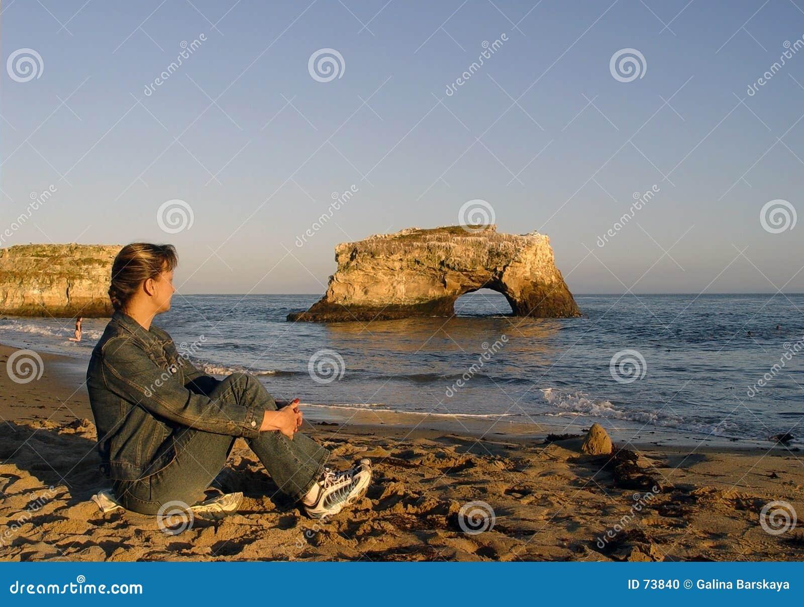 Frau, die auf dem Strand sich entspannt