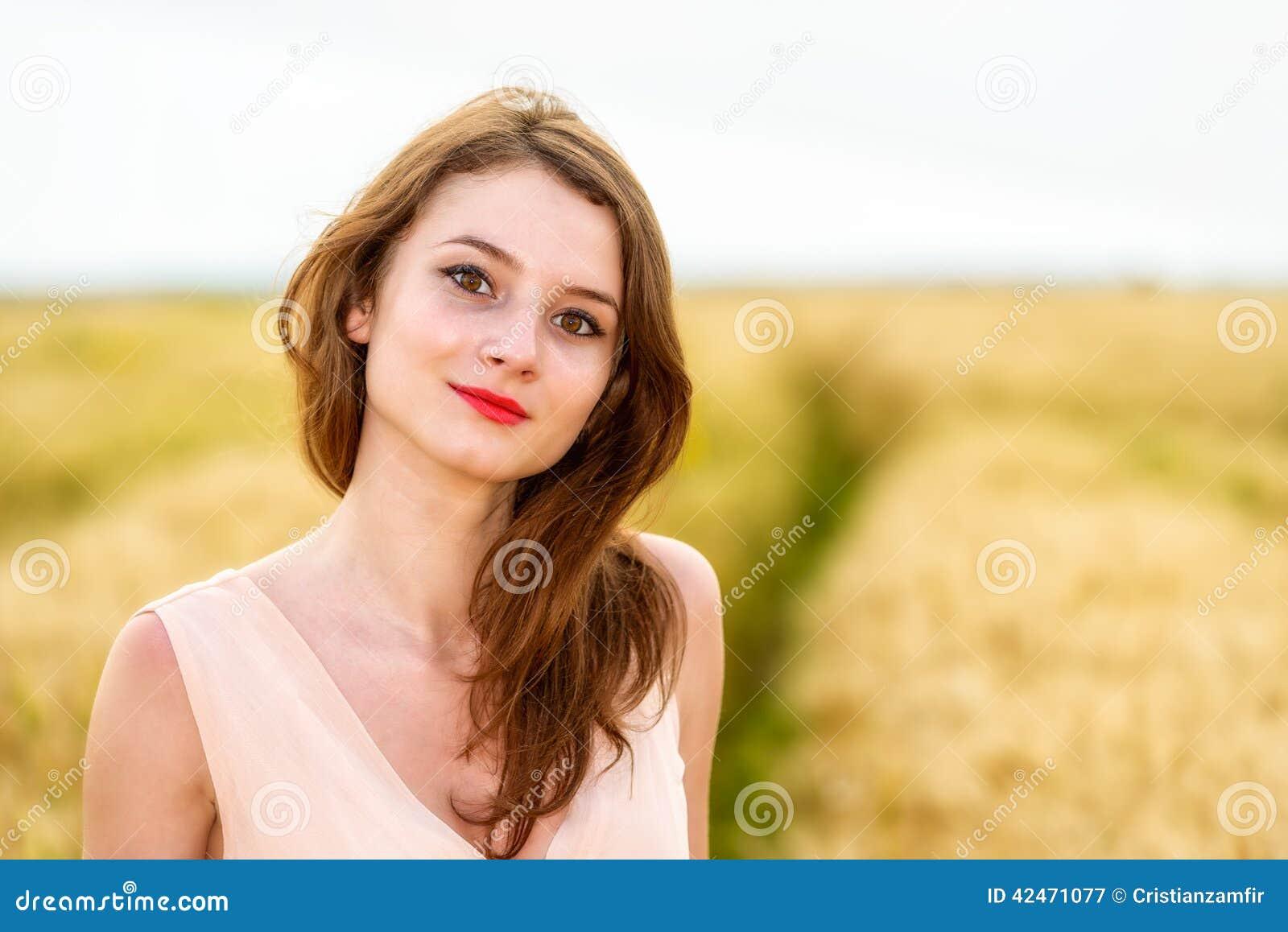 Frau, die auf dem Weizengebiet aufwirft