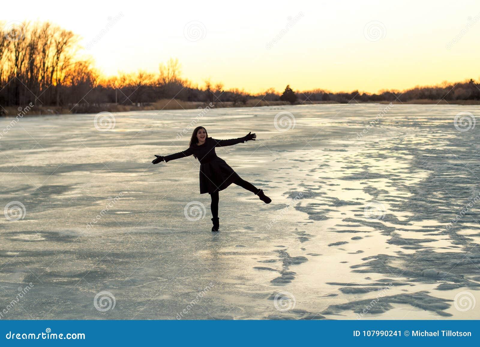 Frau, die auf einem Bein auf dem Eis auf dem gefrorenen Platte River im Winter bei Sonnenuntergang steht