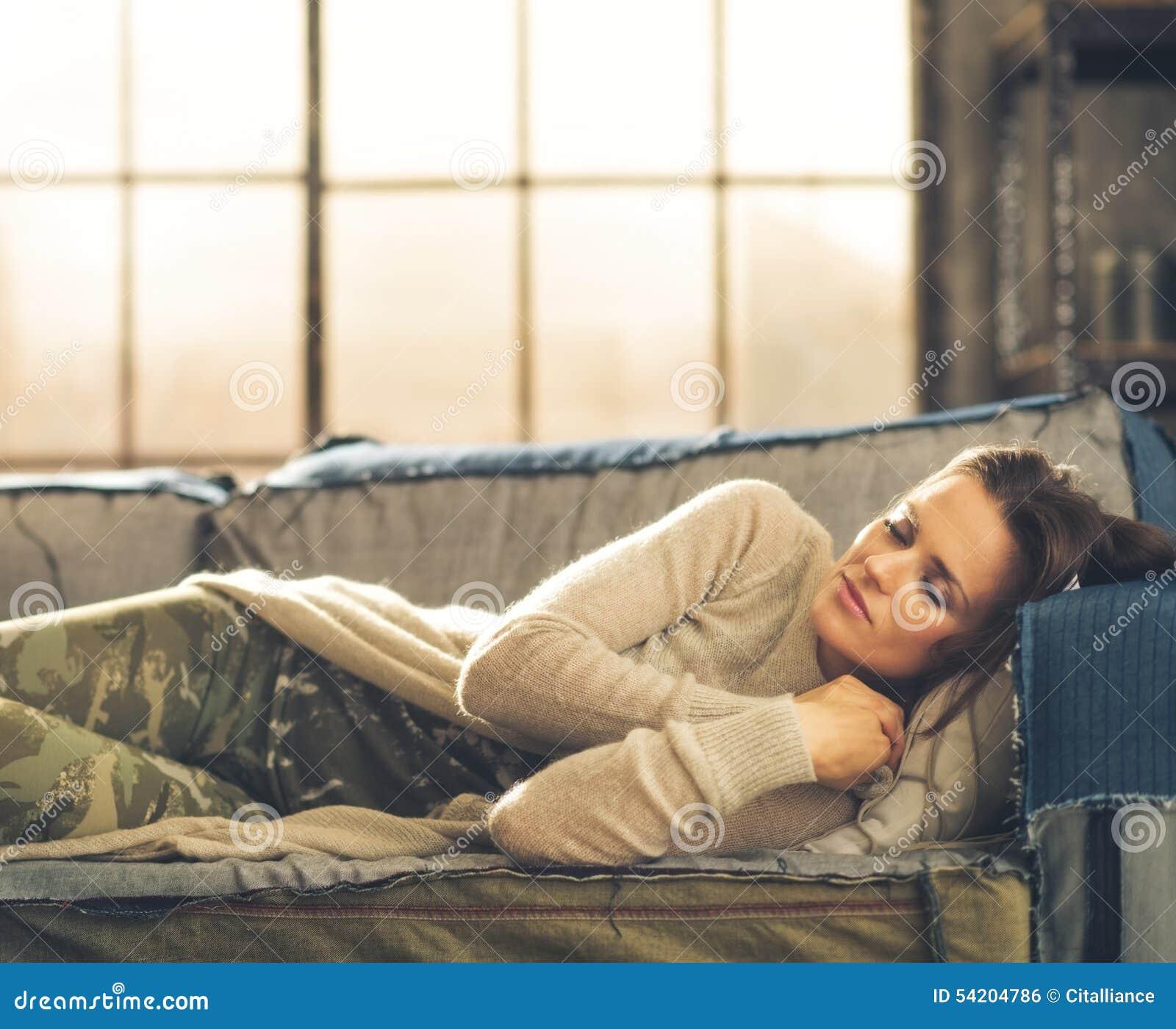 Frau, die auf einem Sofa in einem Stadtdachboden Nickerchen macht