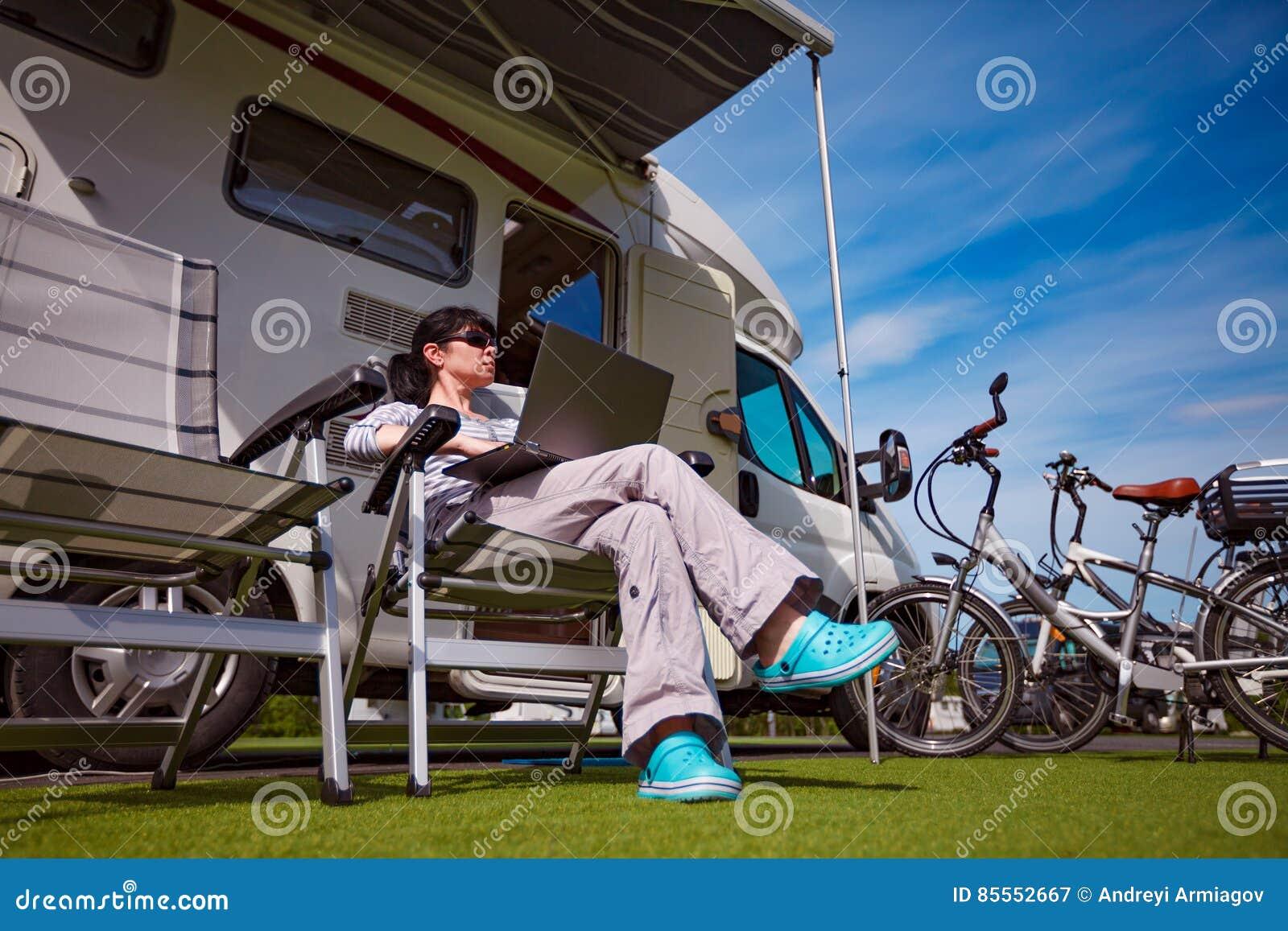 Frau, die auf einem Stuhl nahe dem Camper sitzt und einen Laptop betrachtet