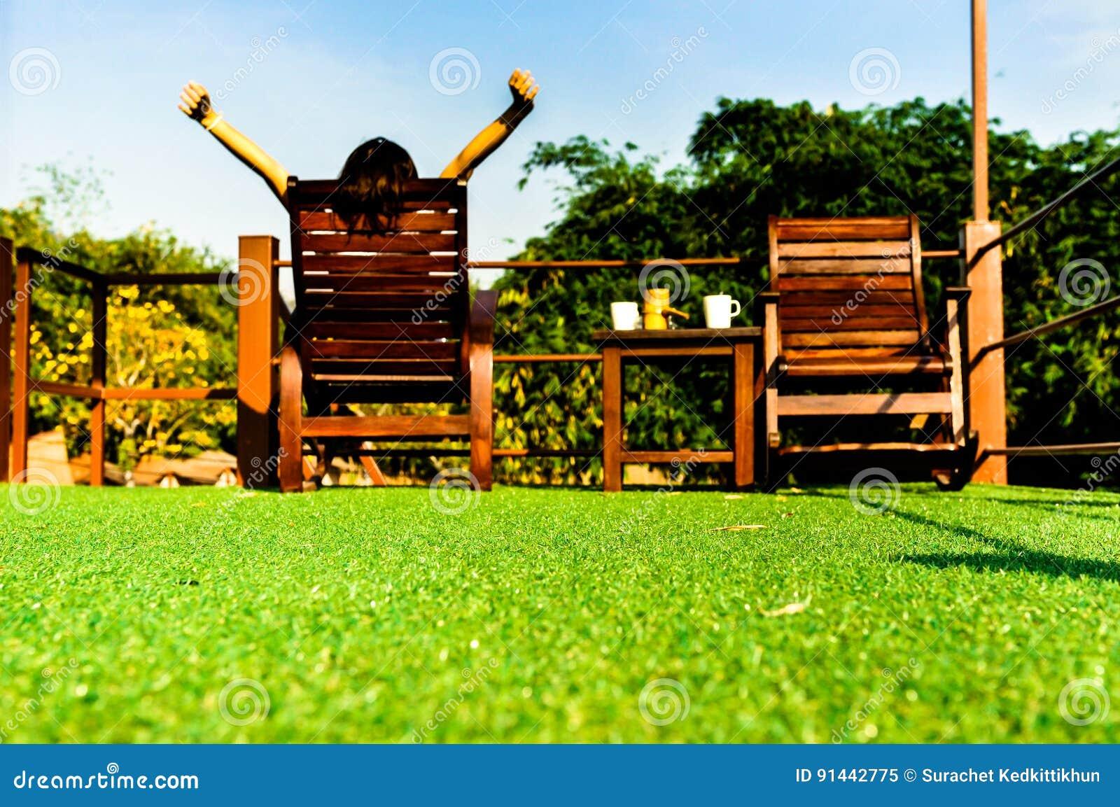Frau, die auf hölzernem sunbed auf grünem künstlichem Gras sich entspannt und den blauen Himmel schaut