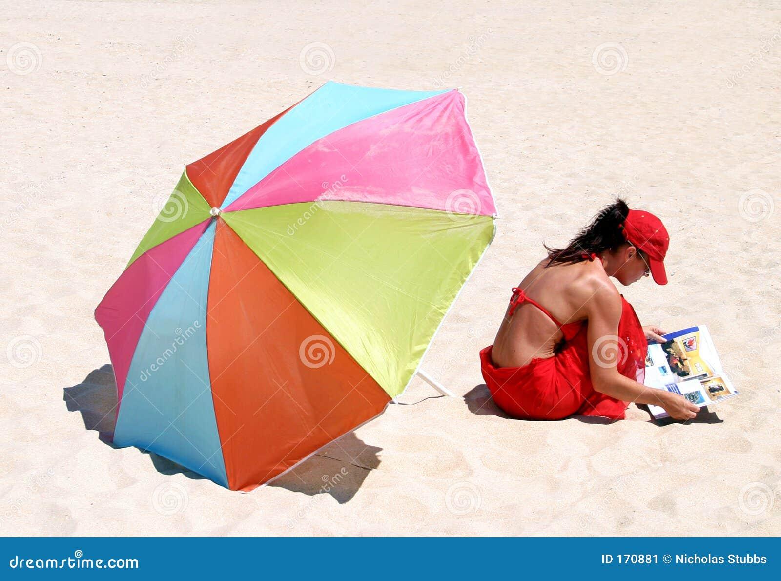 Frau, die auf Strandmesswert sitzt
