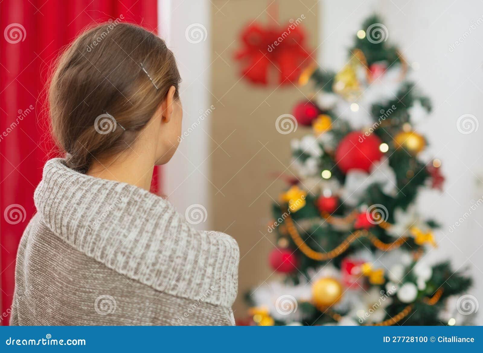 Frau, die auf Weihnachtsbaum schaut. Hintere Ansicht