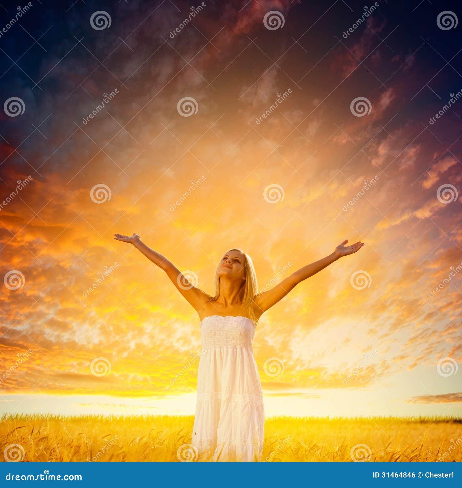 Frau, die auf Weizenfeld über Sonnenuntergang geht