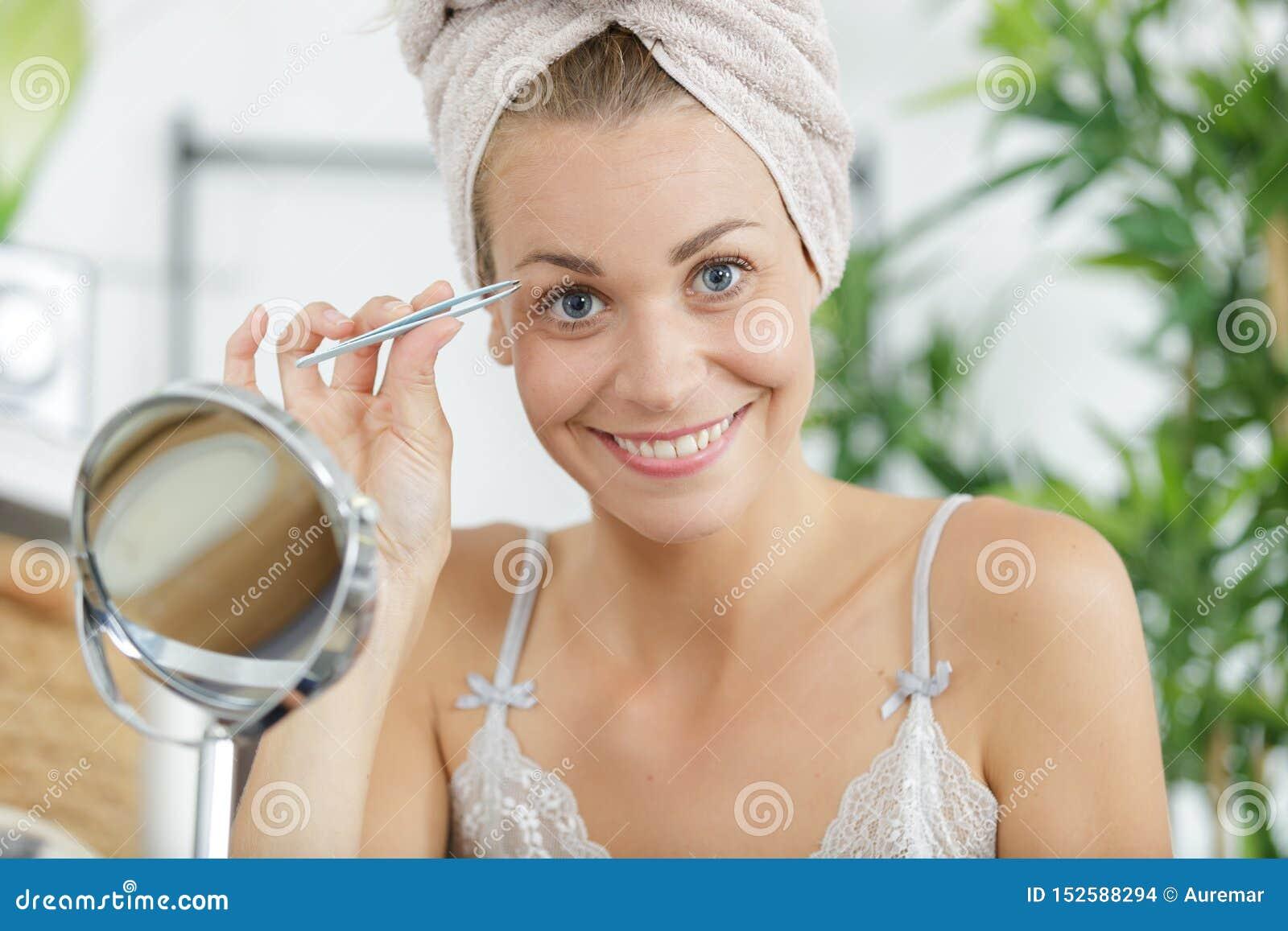 Frau, die Augenbrauen mit Pinzette zupft