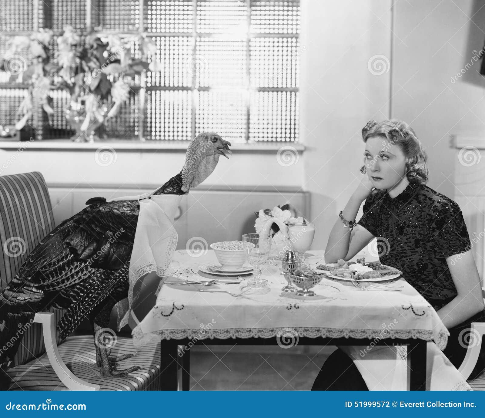 Frau, die bei Tisch Mahlzeit mit Livetruthahn isst (alle dargestellten Personen nicht länger leben und kein Zustand existiert Lie