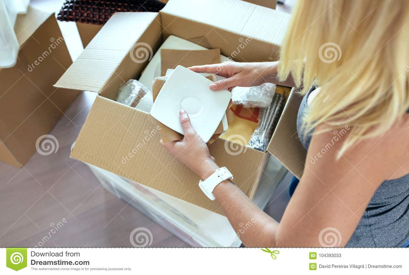 Frau, die bewegliche Kästen auspackt