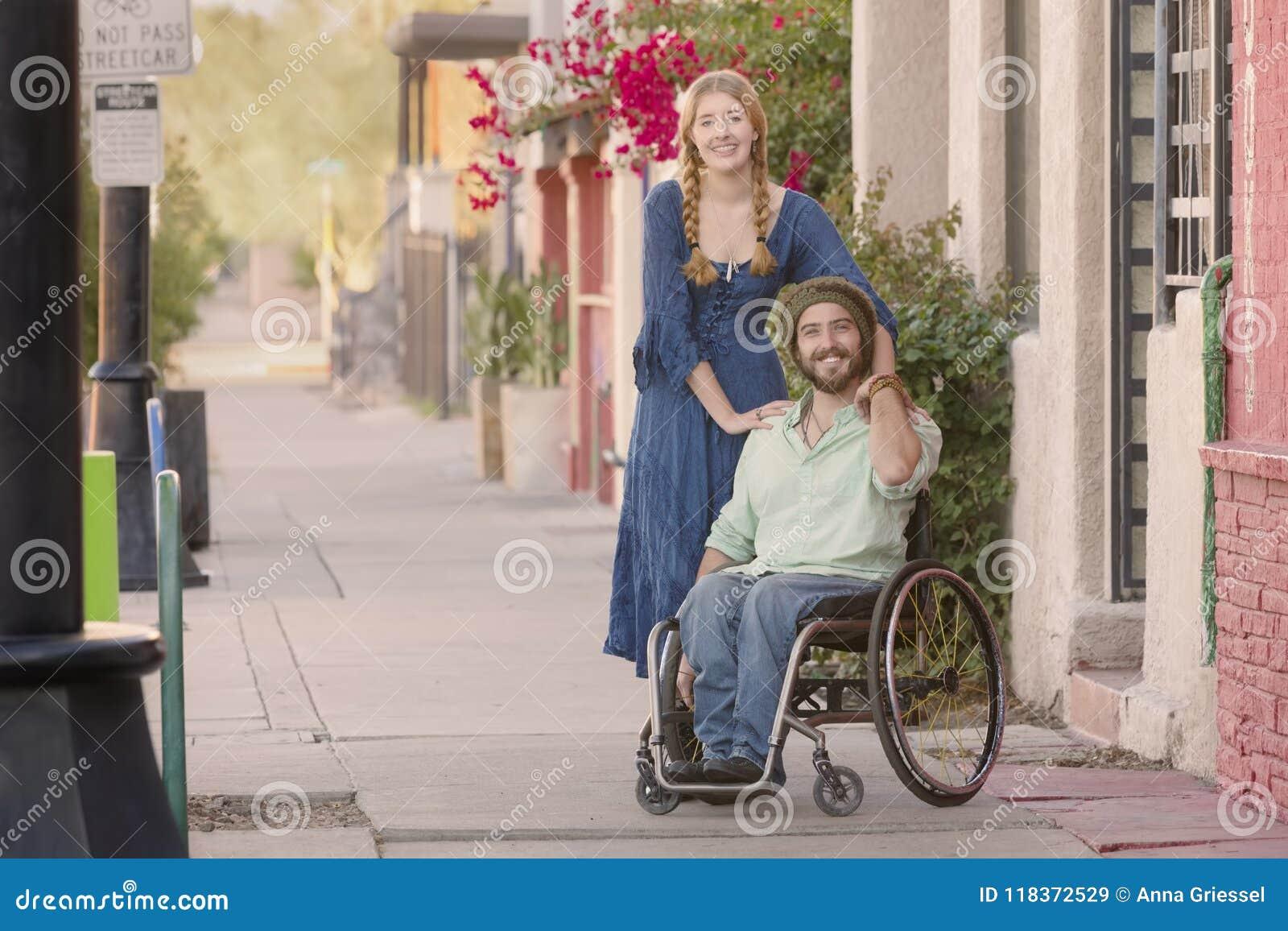 Frau, die blaues Kleid und Mann im Rollstuhl trägt