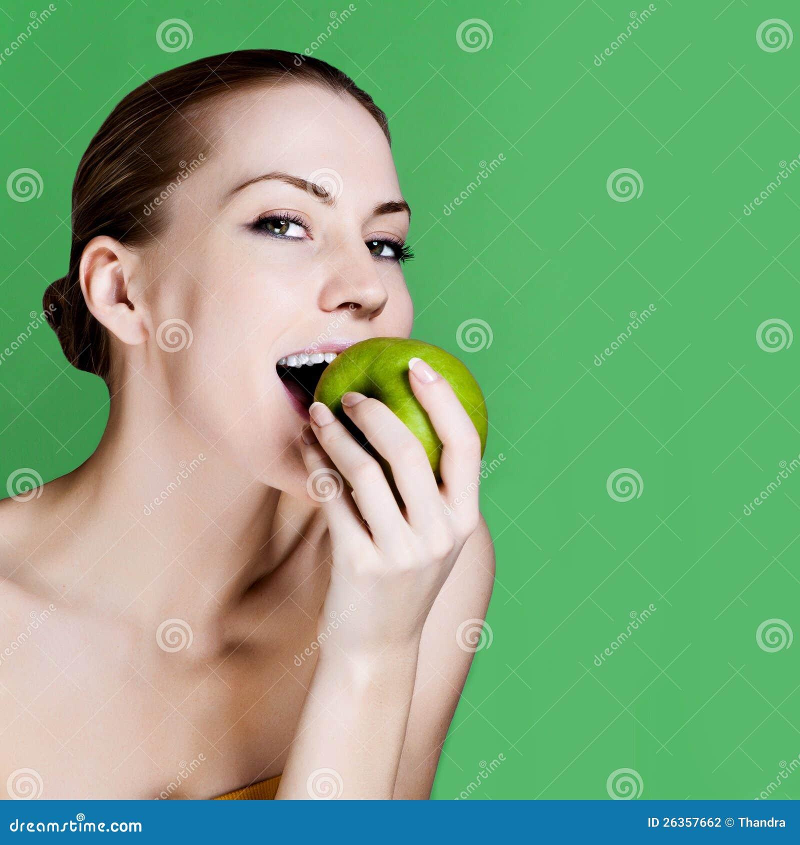 Frau, die den Apfel lächelt auf grünem Hintergrund isst.