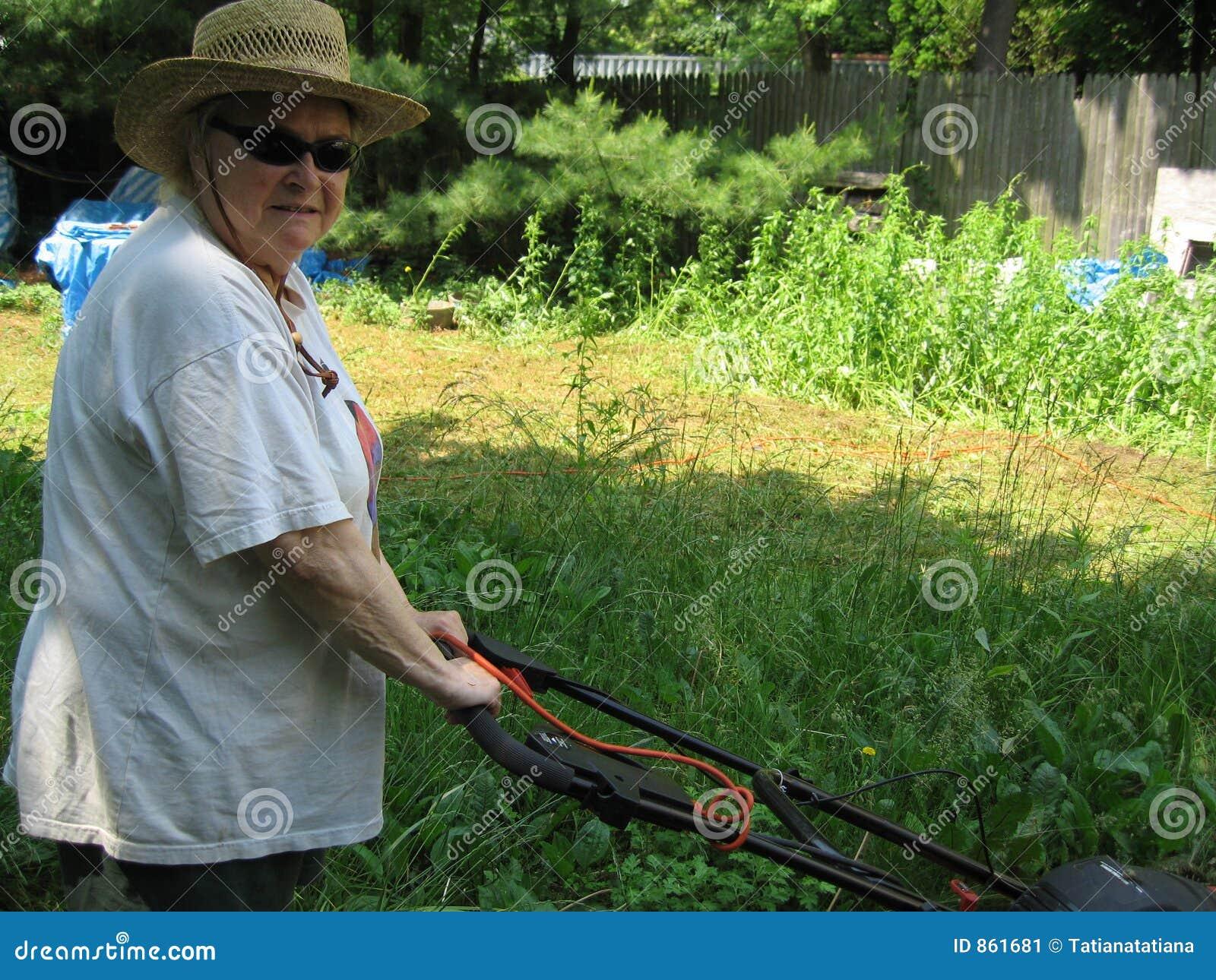 Frau, die den Rasen mäht