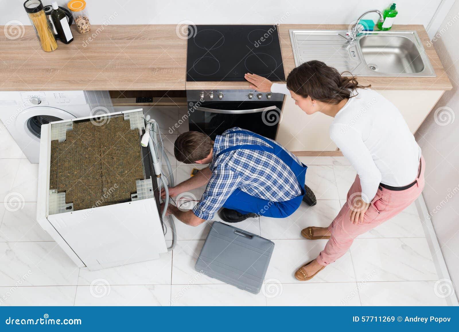 Frau, die den Schlosser Repairing Dishwasher betrachtet