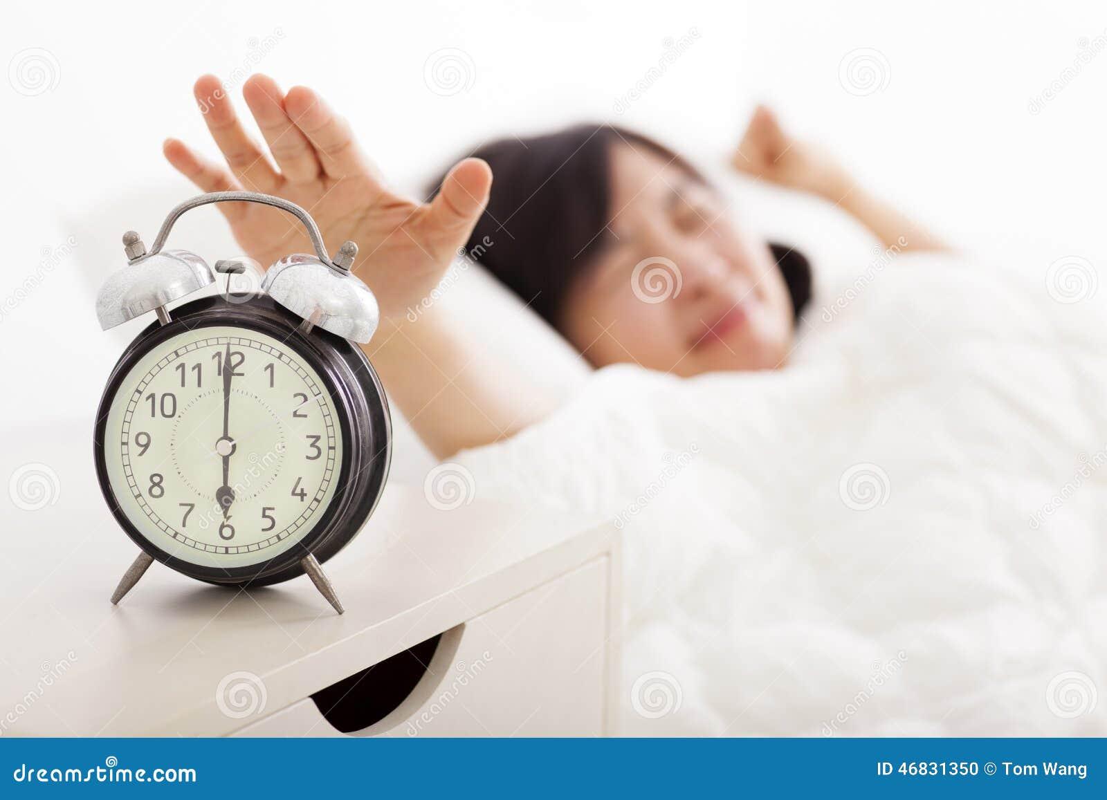Frau, die den Wecker auf dem Bett abstellt