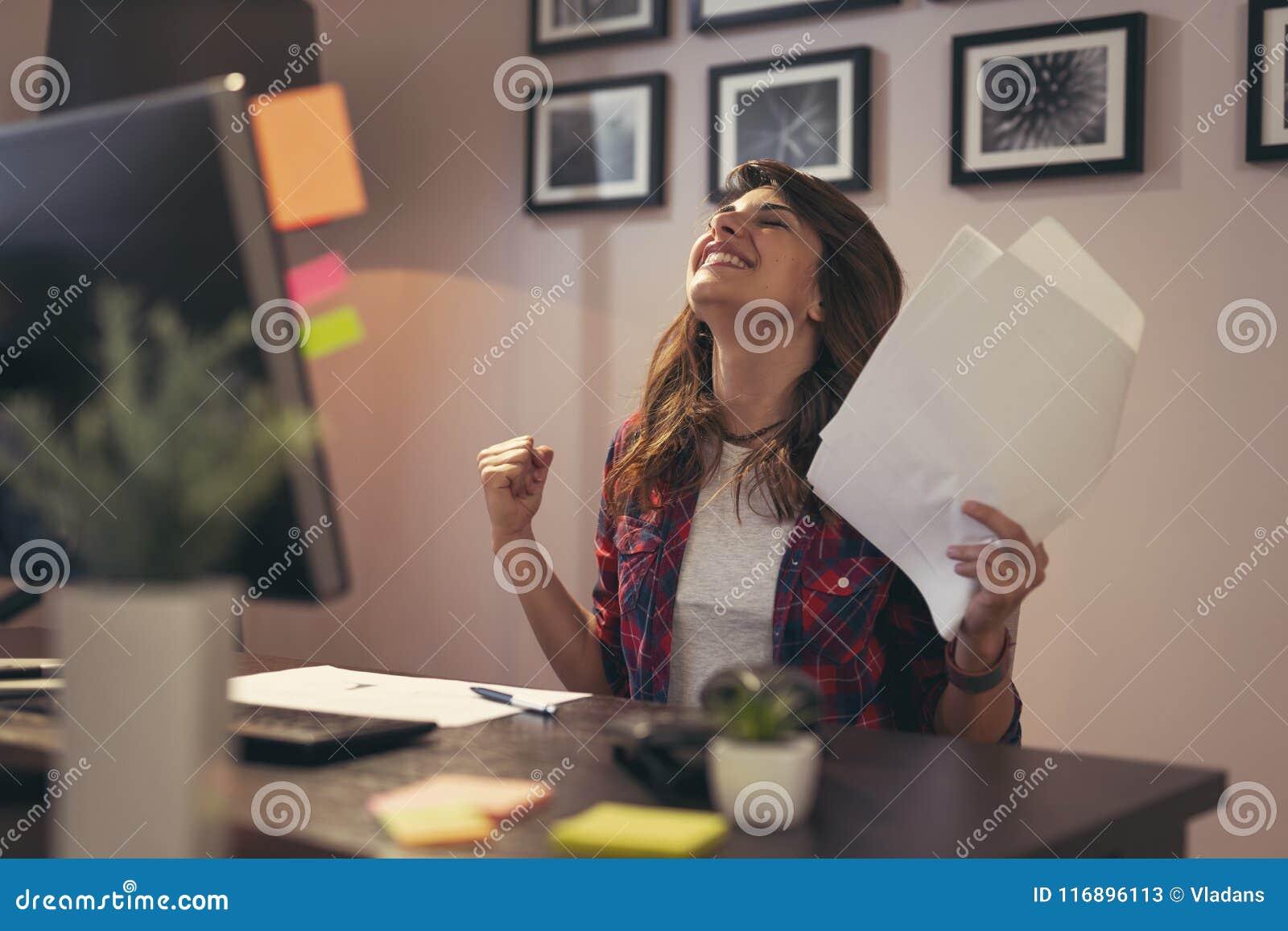 Frau, die Dokumente froh nach Geschäftserfolg verwahrt