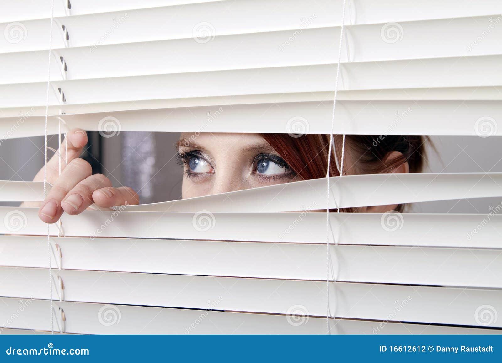 Frau, die durch Fenstervorhänge schaut