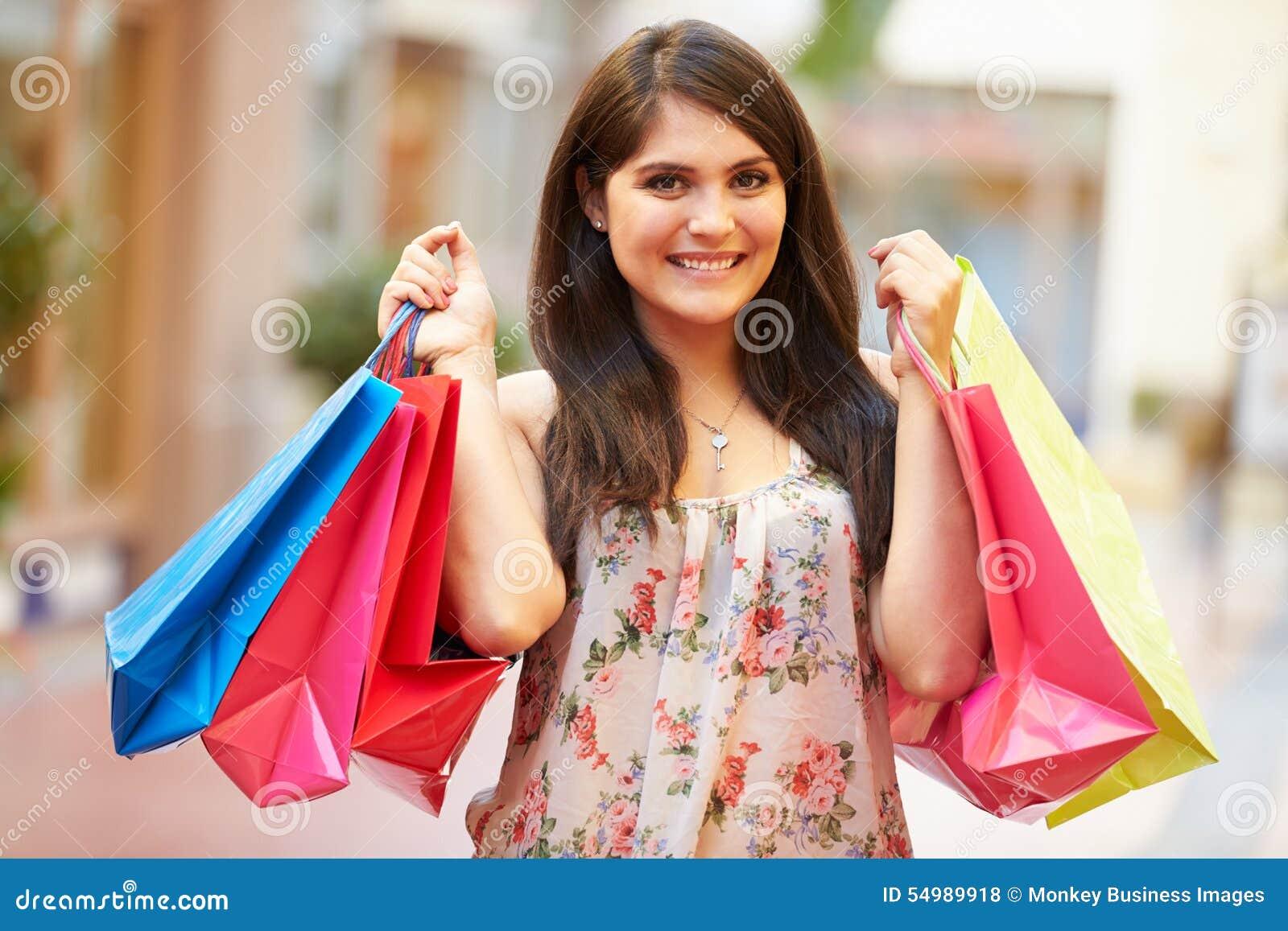 Frau, die durch Mall-tragende Einkaufstaschen geht