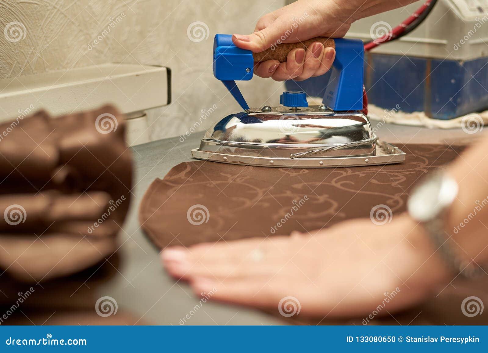 Frau, die ein braunes Material mit einem Eisen auf einem Bügelbrett streicht