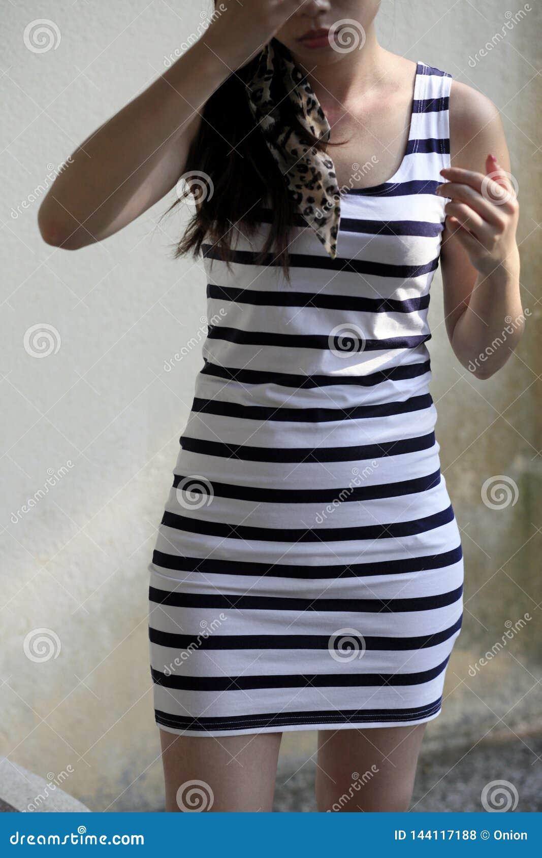 frau, die ein gestreiftes kleid in schwarzweiss trägt