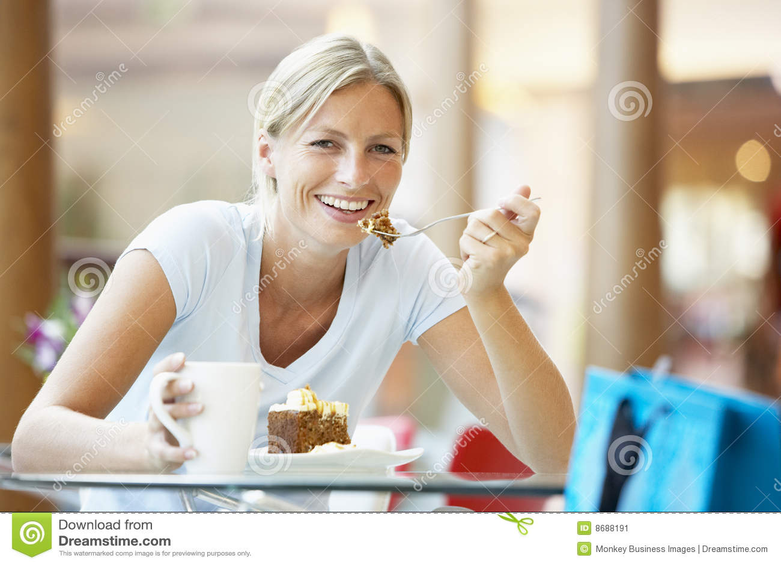 Frau, die ein Stück des Kuchens am Mall isst