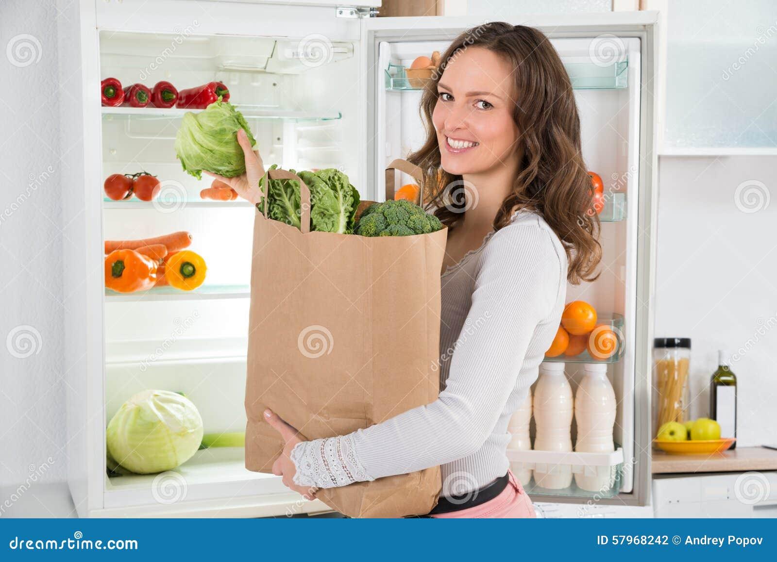 Frau, die Einkaufstasche mit Gemüse hält