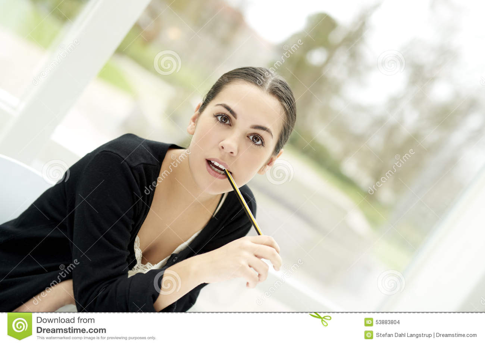 Frau, die gerade voran mit Bleistiftende im Mund anstarrt