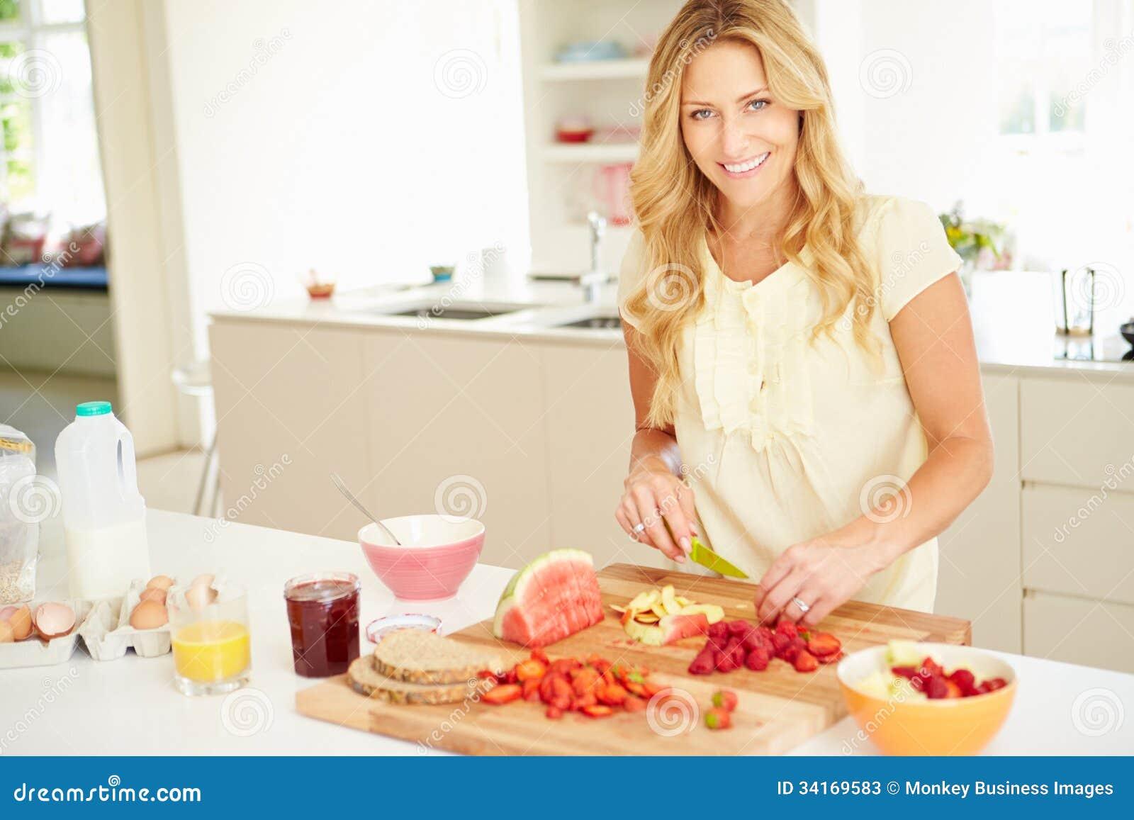 Frau, die gesundes Frühstück in der Küche zubereitet