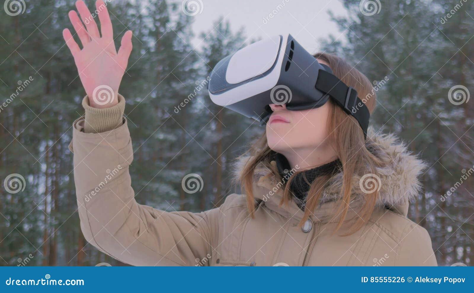 Frau, die Gläser der virtuellen Realität im Winterwald verwendet