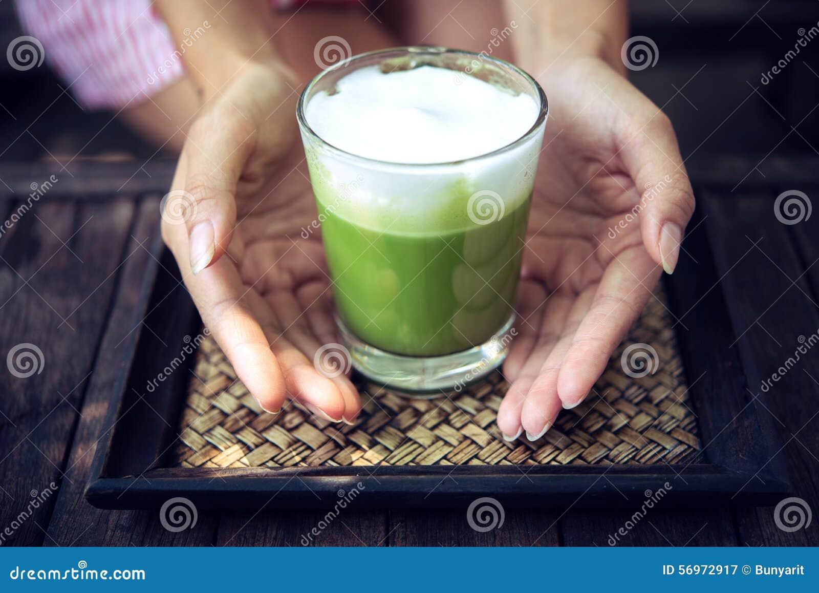 Frau Die Grüner Tee Matcha Latte Auf Holztisch Hält Stockbild