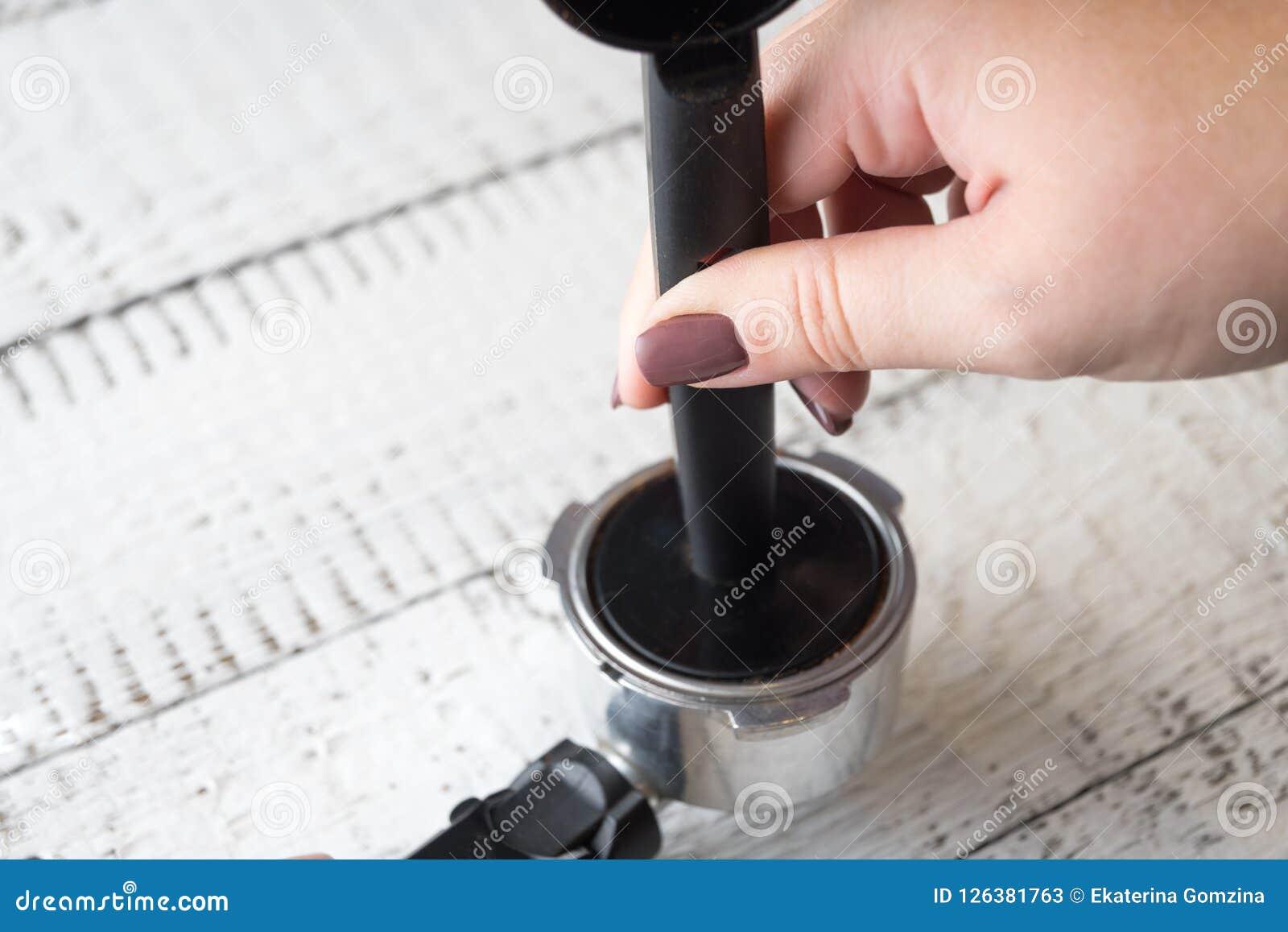 Frau, die grinded Kaffee in einem Gruppenanführer einer Kaffeemaschine bedrängt, um einen Morgenespresso zu machen Frühstück und