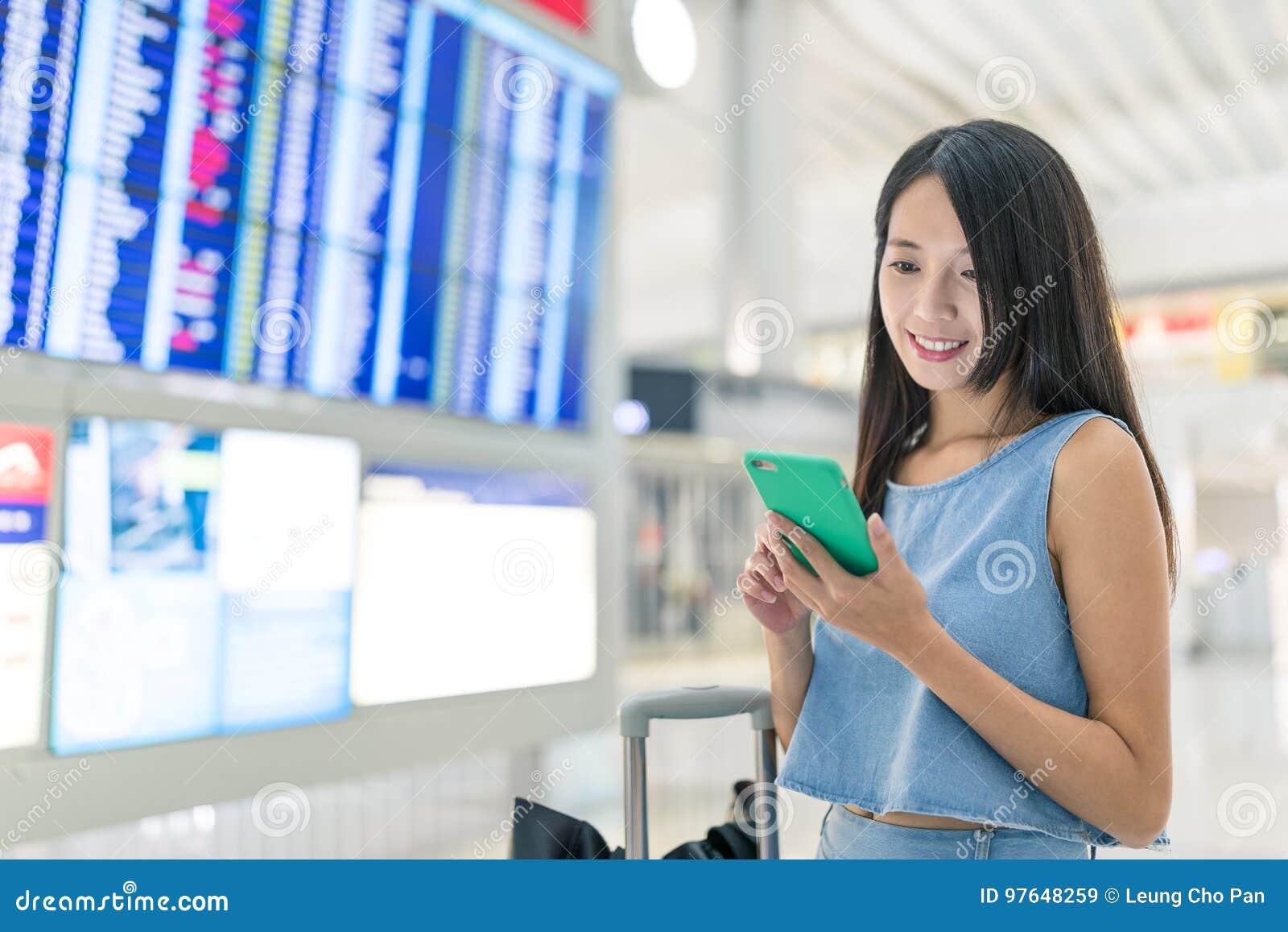Frau, die Handy verwendet, um ihren Flugplan zu überprüfen