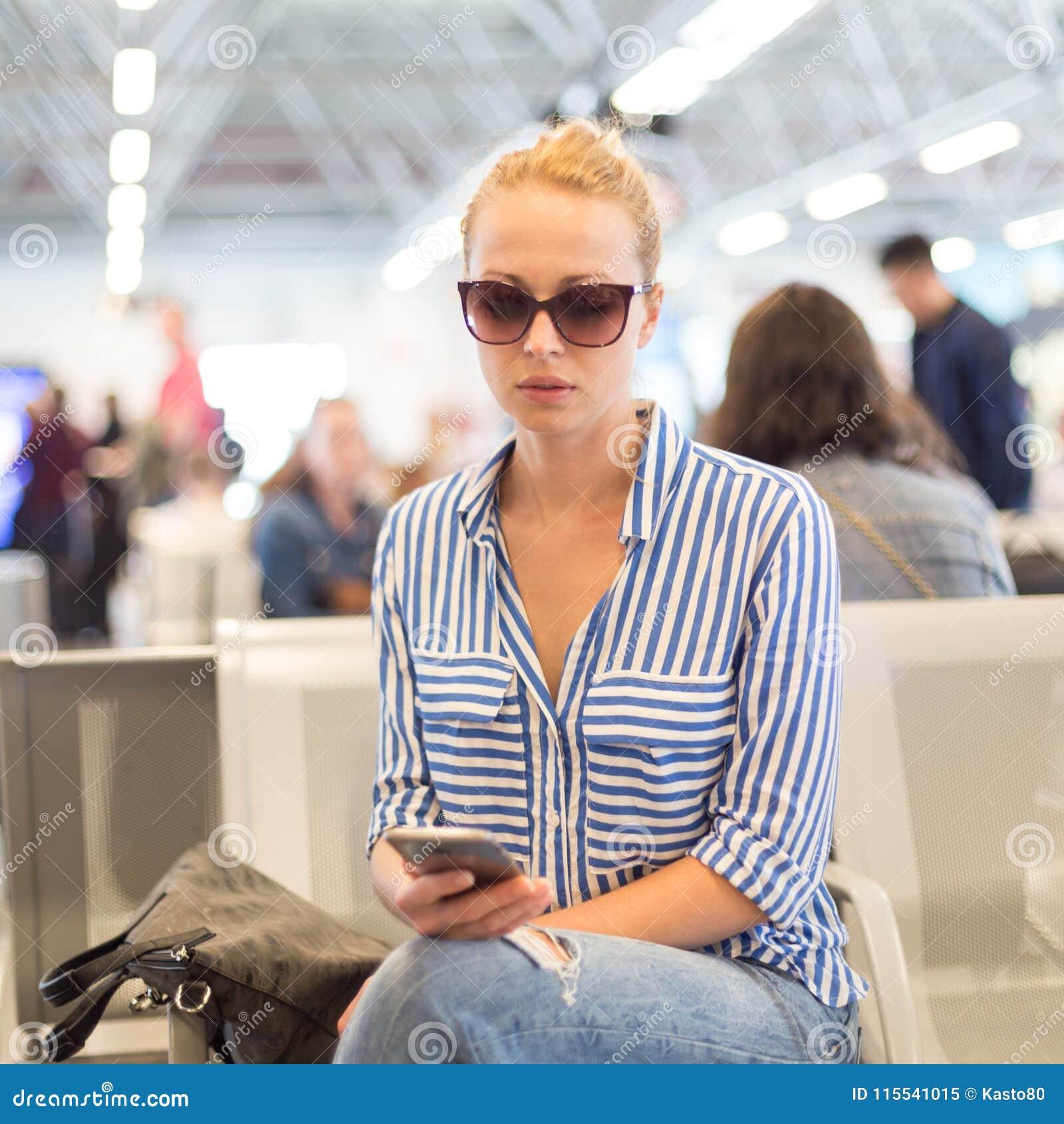 Frau, Die Ihren Handy Bei Der Aufwartung, Um Ein Flugzeug