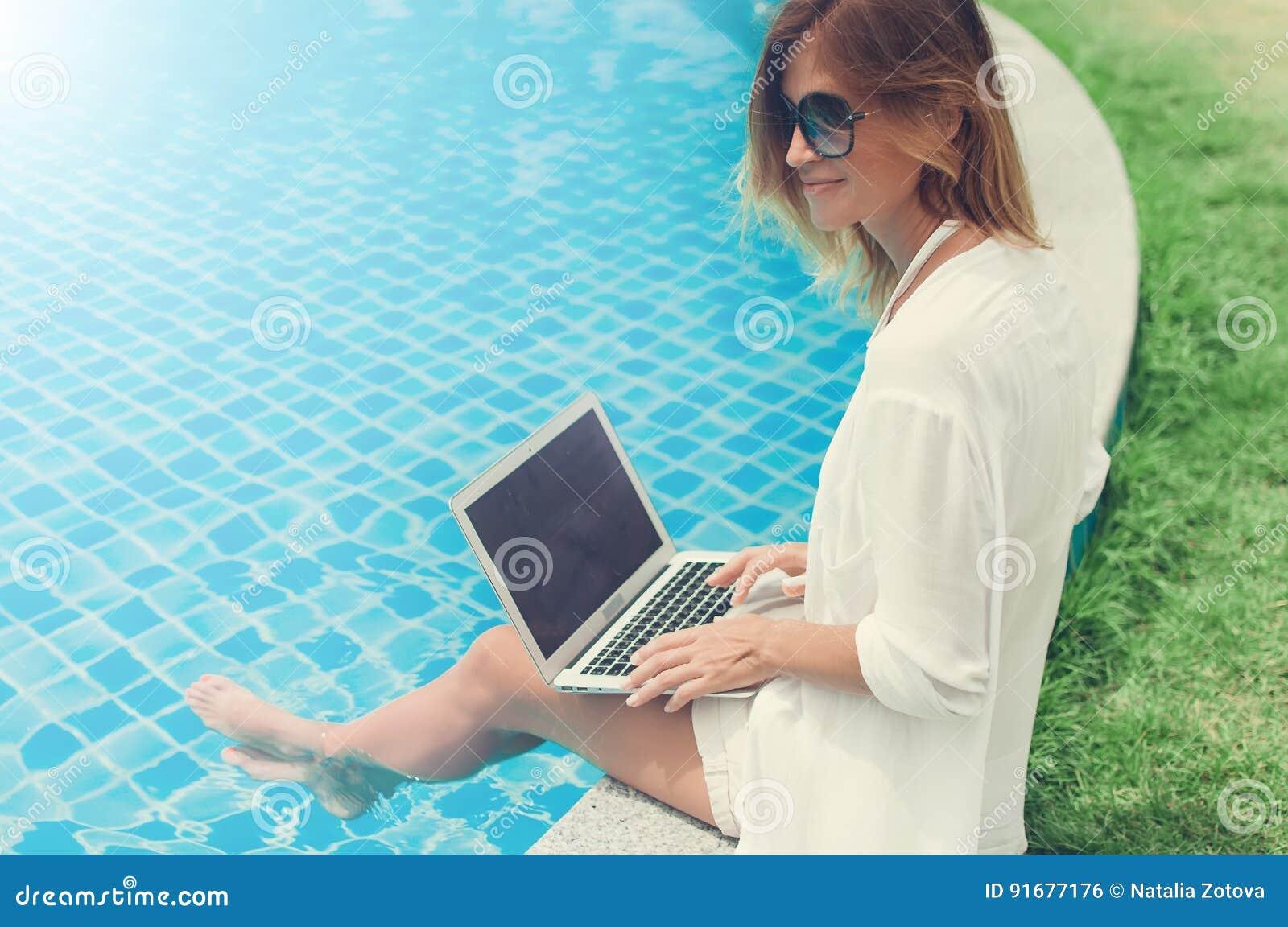 e822c2f83de6 Frau, Die An Ihrer Laptop-Computer Sitzt Am Poolside Arbeitet ...