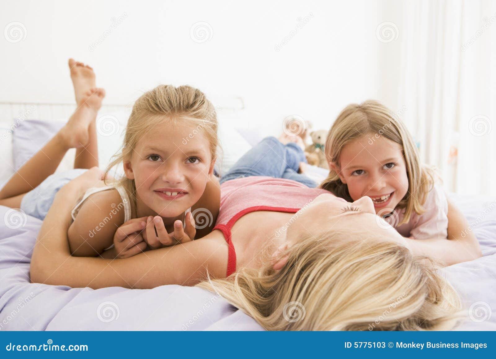 frau die im bett mit dem l cheln mit zwei jungen m dchen liegt stockfotos bild 5775103. Black Bedroom Furniture Sets. Home Design Ideas