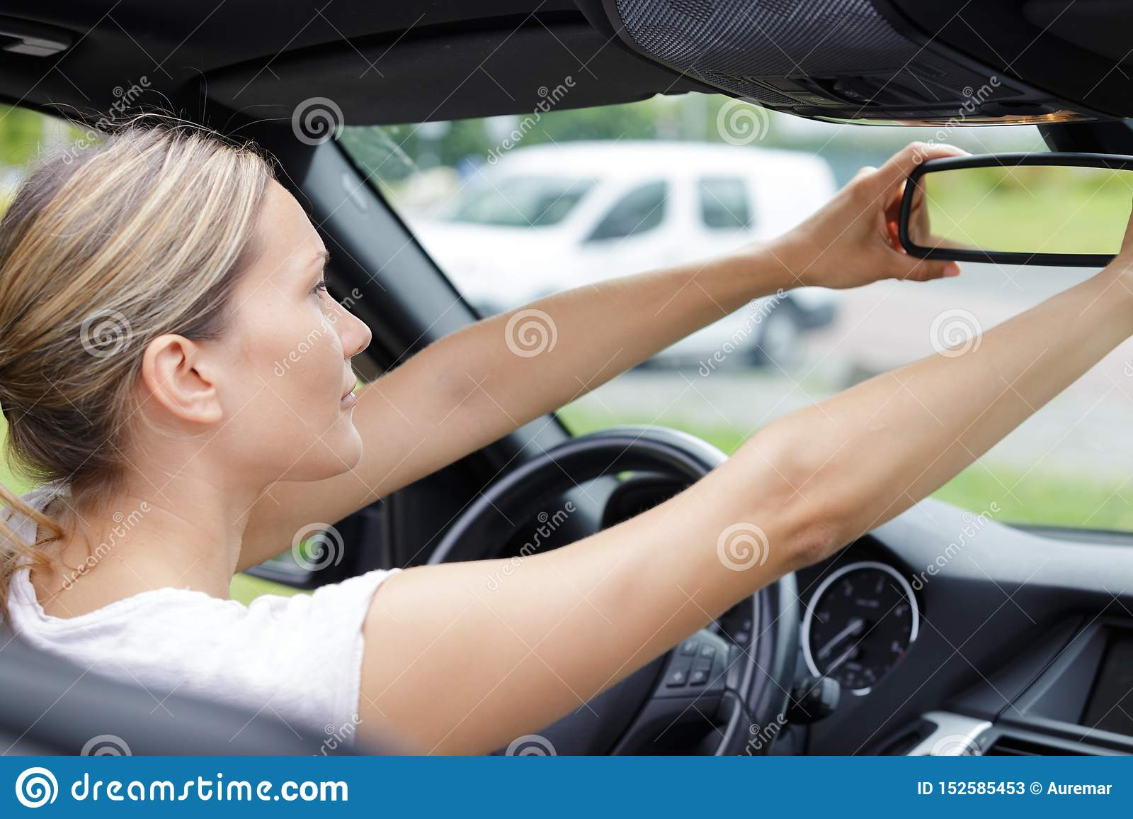 Frau, die im Rückspiegelauto schaut