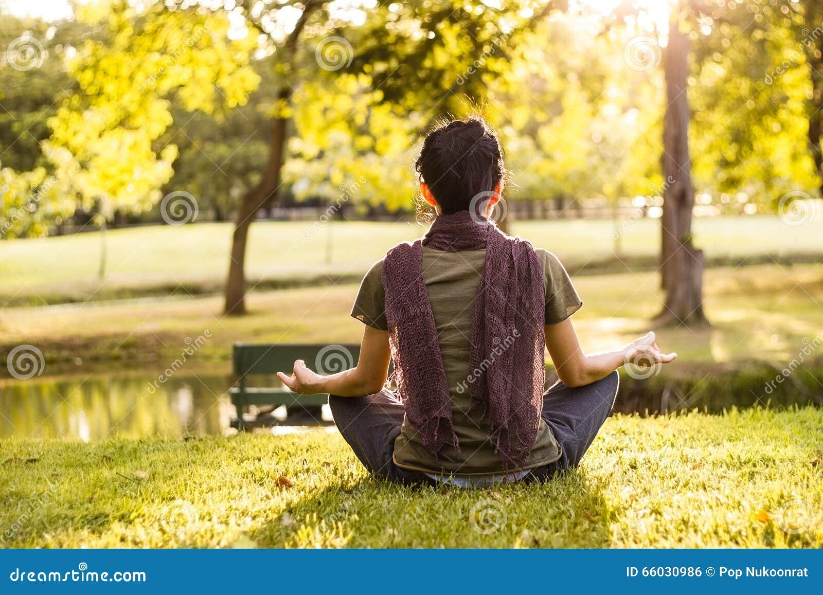 Frau, die im Sonnenlicht im Sommerpark meditiert