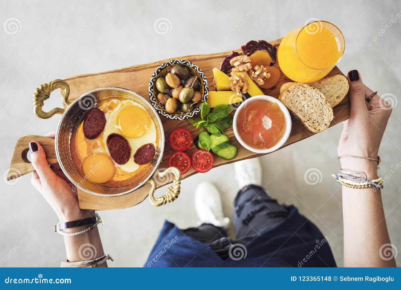 Frau, die köstliches traditionelles türkisches Frühstück auf Schneidebrett trägt