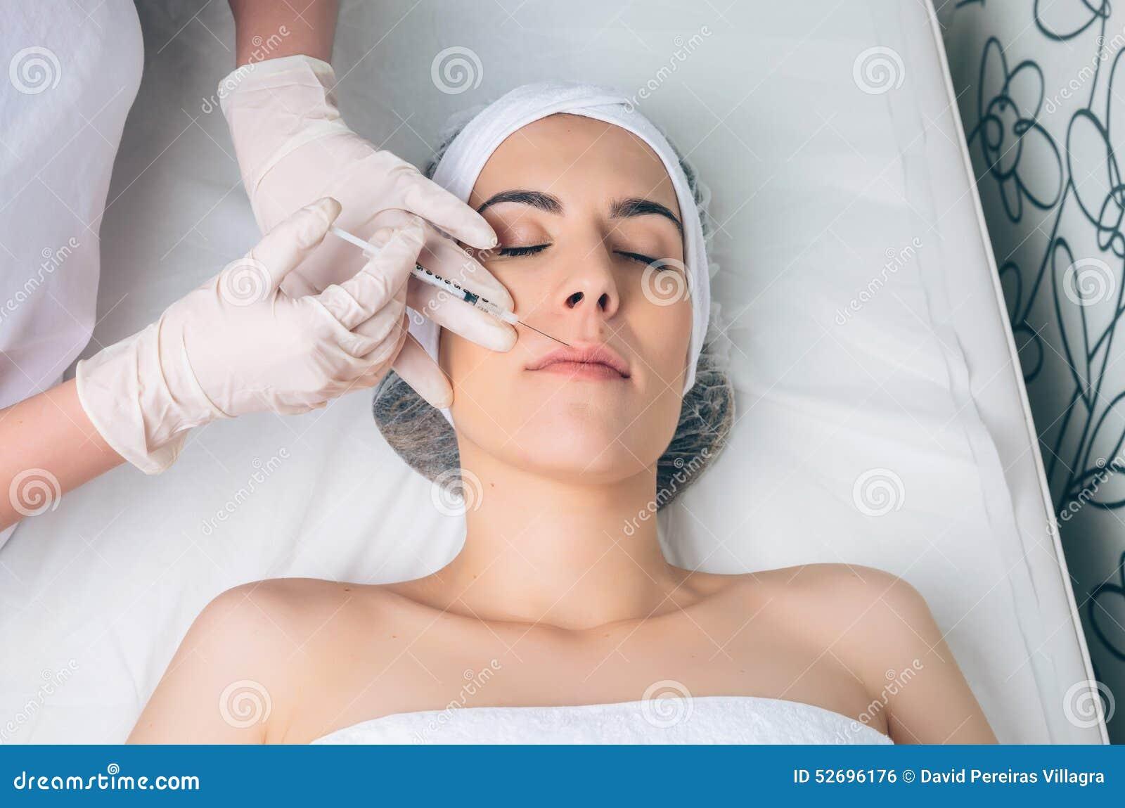 Frau, die an kosmetische Einspritzung in ihrem Gesicht erhält
