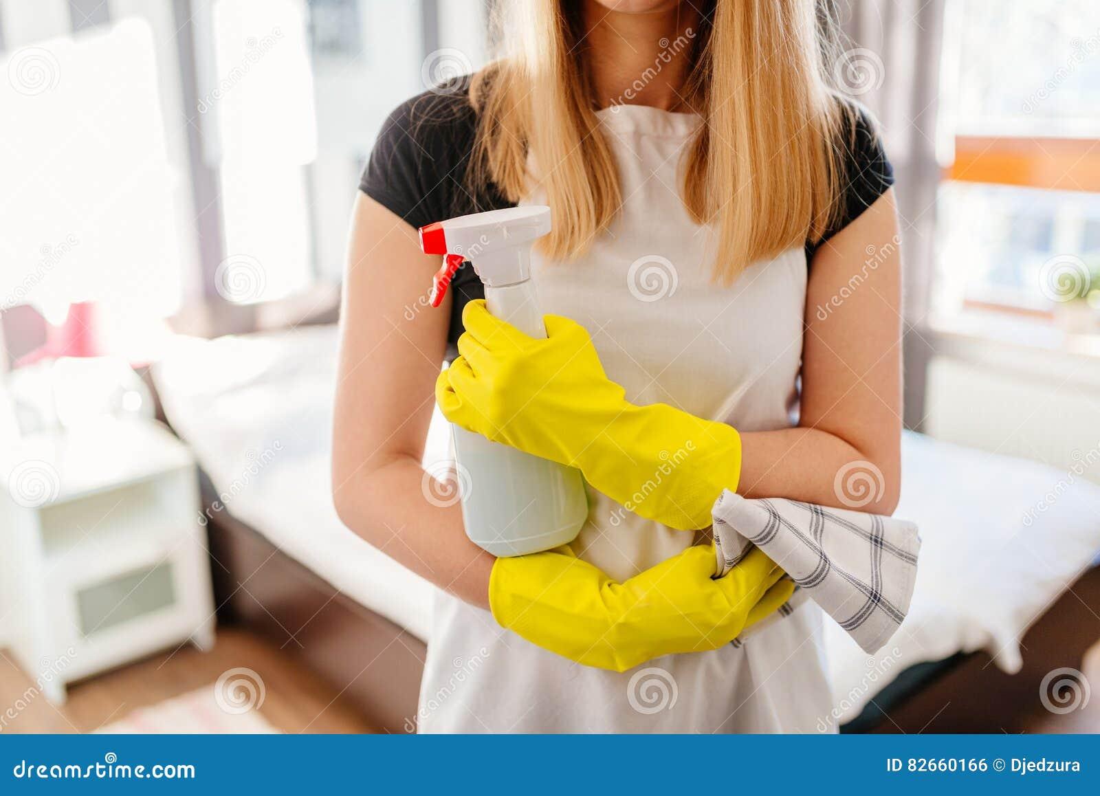 Frau, die Lappen- und Sprühflaschereinigungsmittel hält