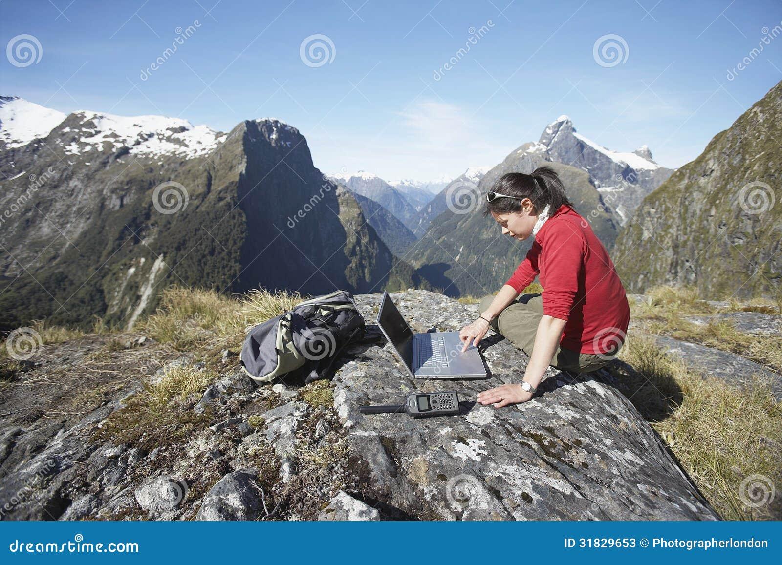 Frau, die Laptop auf Boulder gegen Berge verwendet