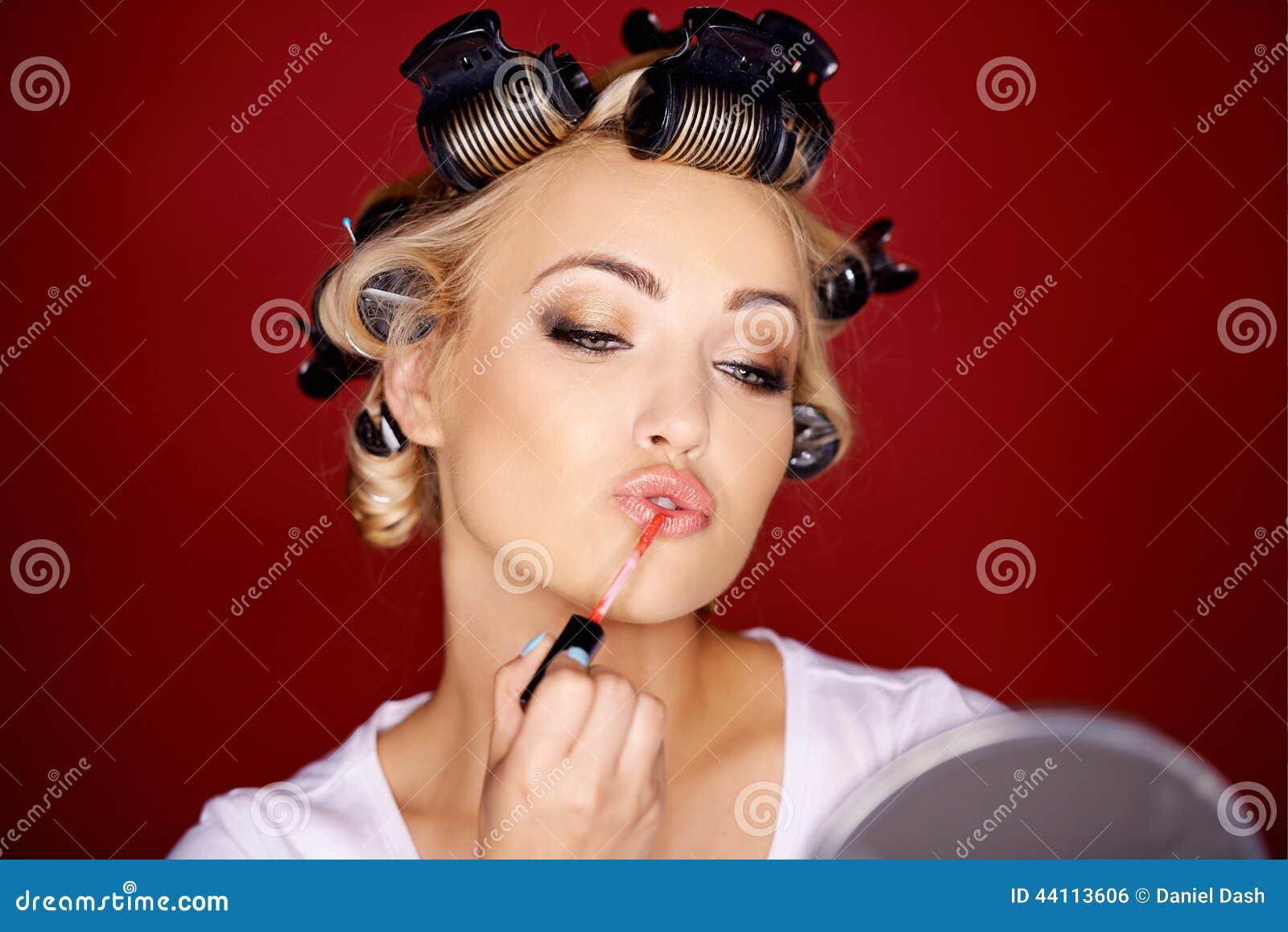 Frau, die Make-up mit ihrem Haar in den Lockenwicklern anwendet