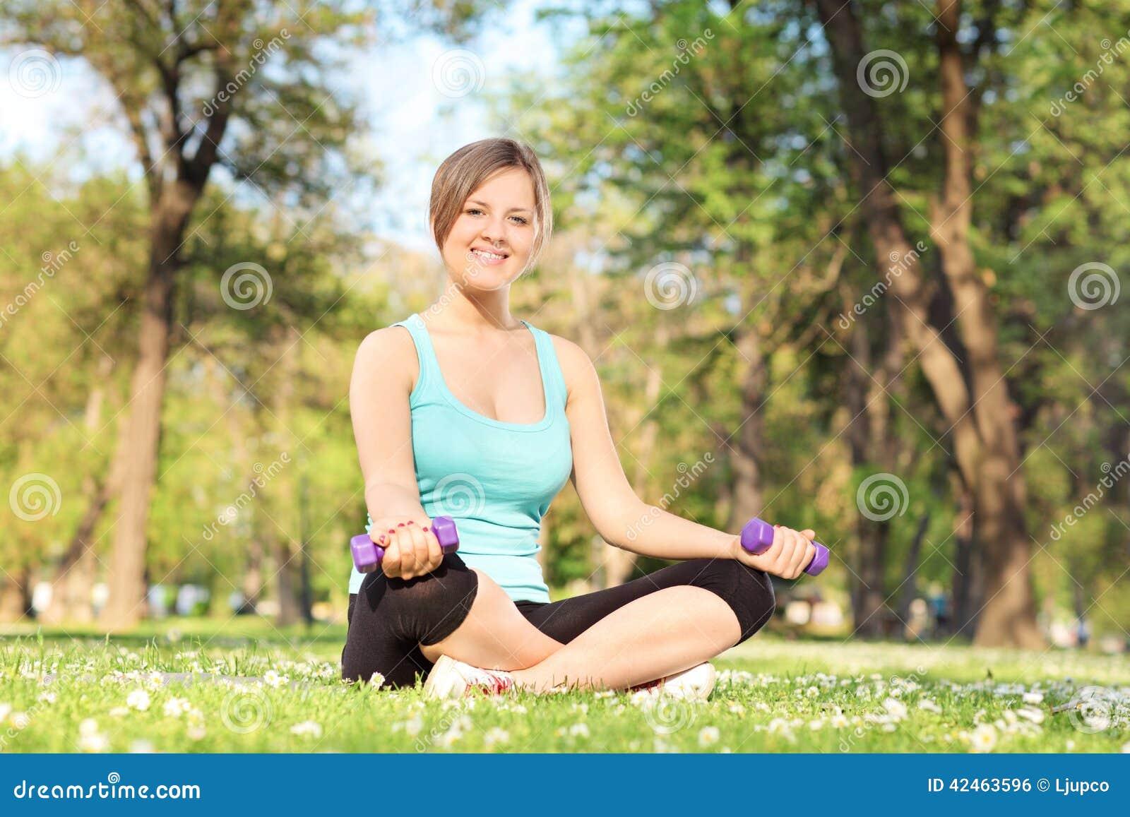 Frau, die mit Dummköpfen im Park trainiert