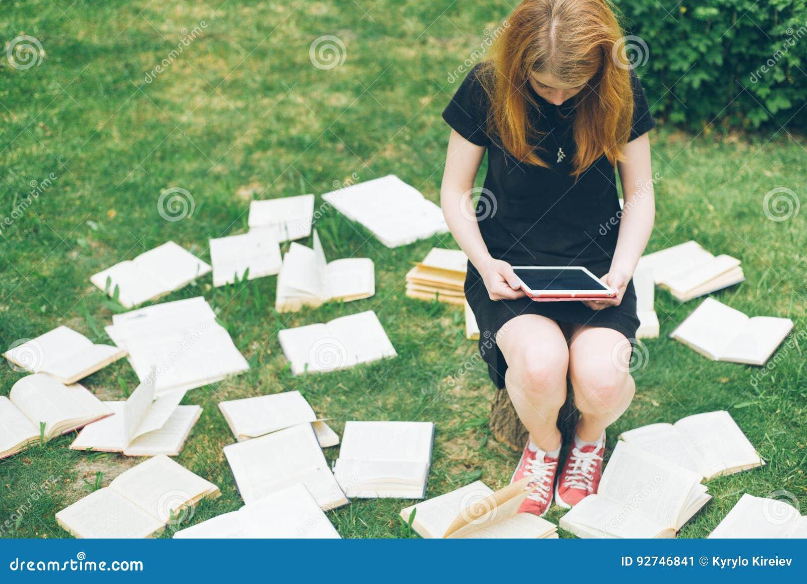Frau, die mit ebook Leser und Buch lernt Wahl zwischen moderner pädagogischer Technologie und traditioneller Weisenmethode Mädche