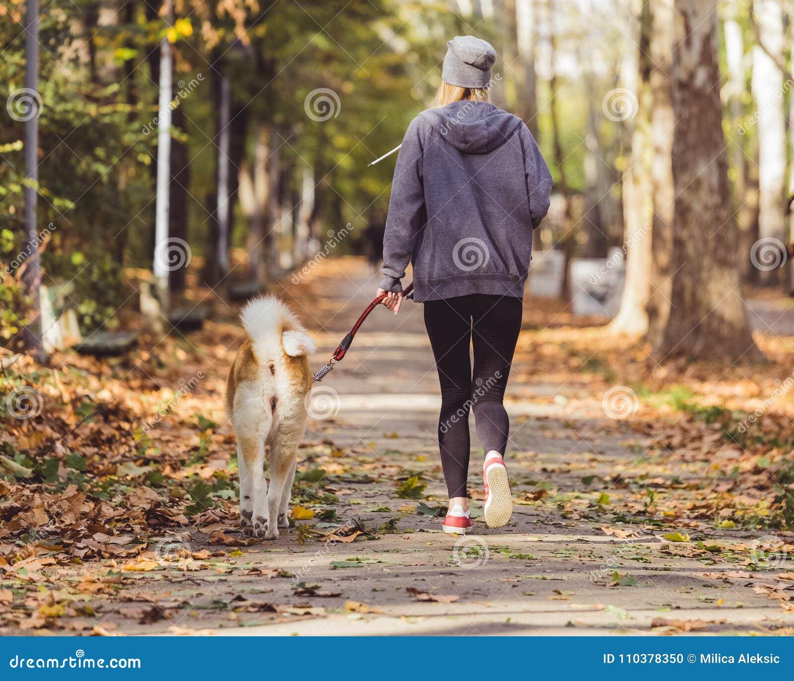 Frau, die mit ihrem Hund im Park läuft und geht
