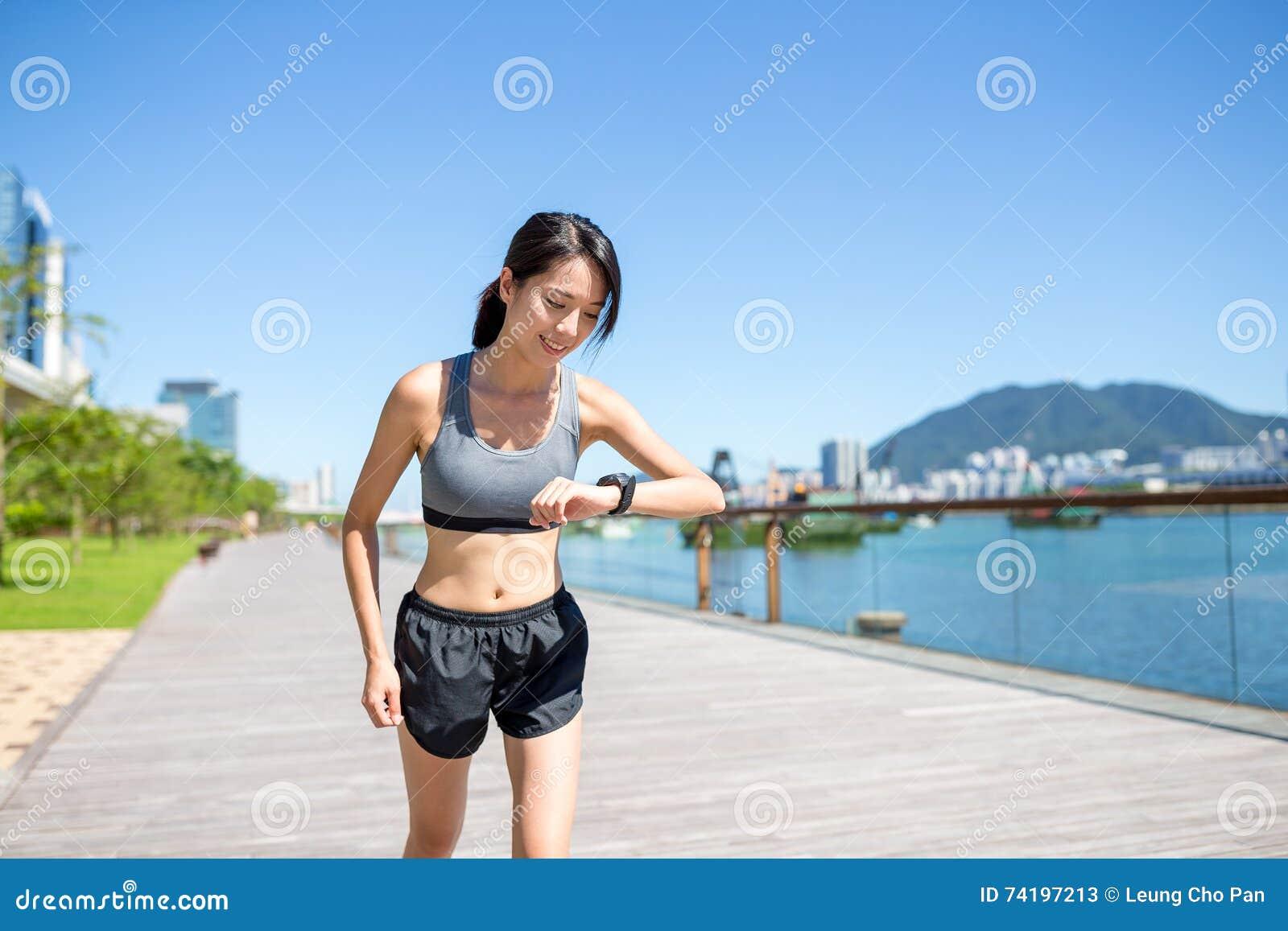 Frau, die am Morgen läuft und die Aufzeichnung auf intelligenter Uhr überprüft