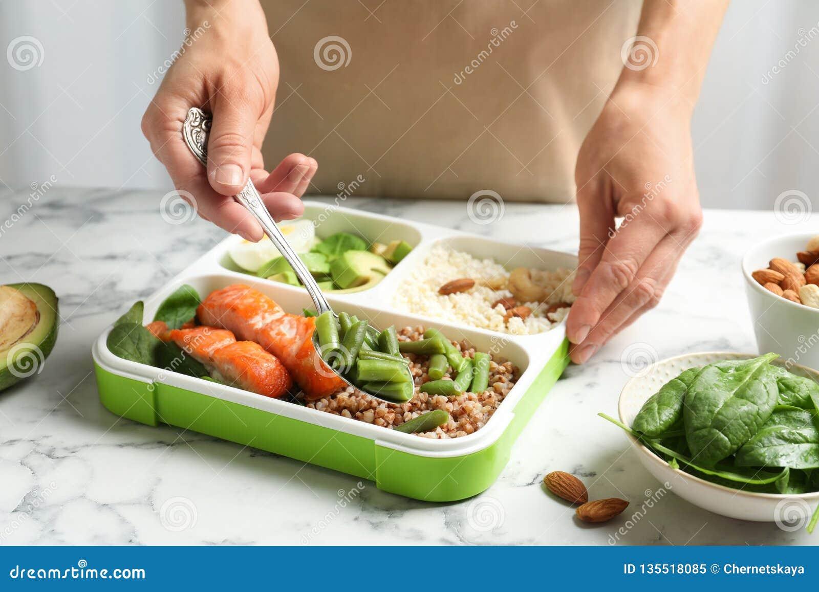 Frau, die natürliche Proteinnahrung in Behälter setzt