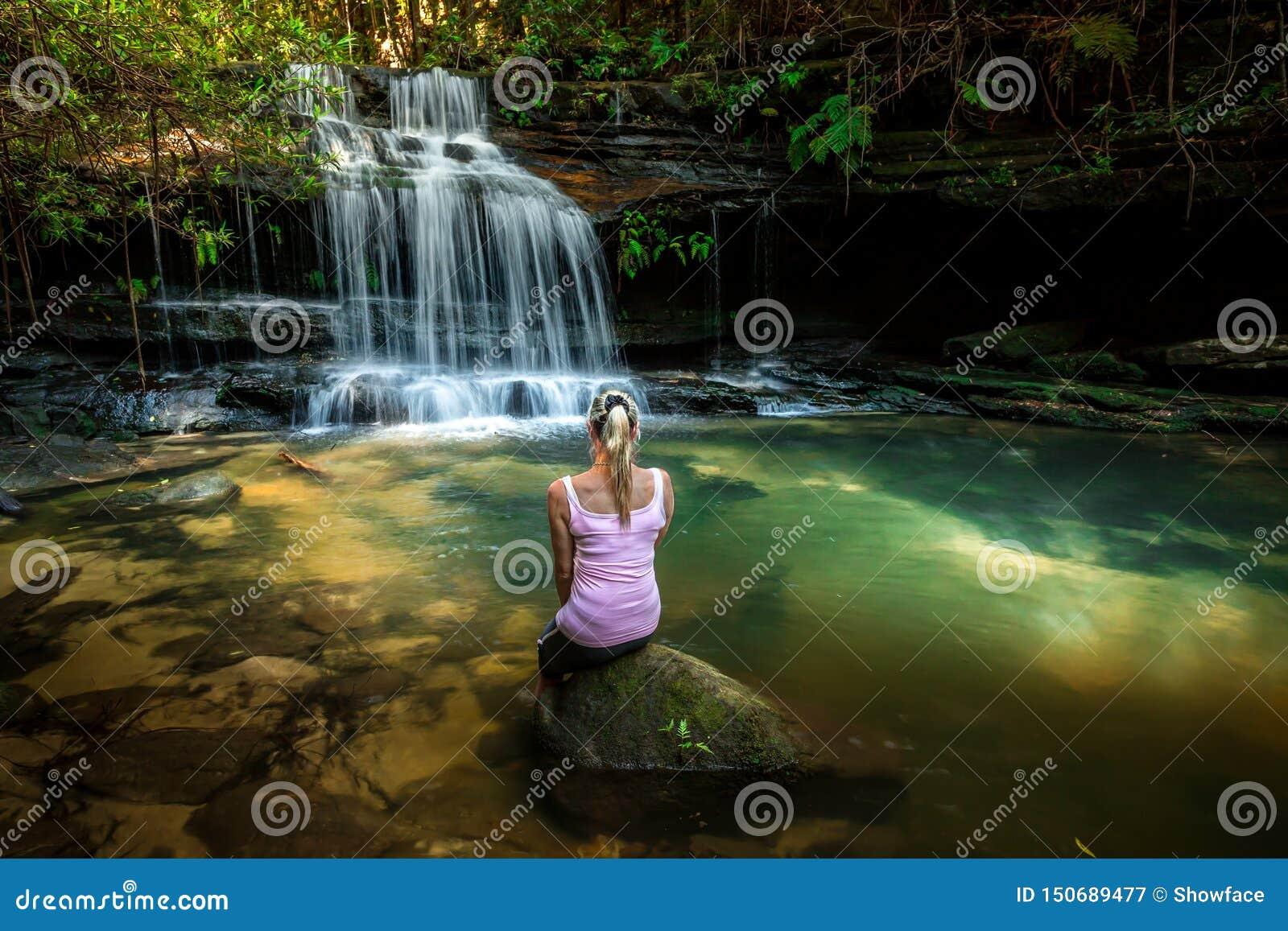Frau, die Natur genie?t Geschecktes Sonnenlicht am Wasserfallfelsenpool