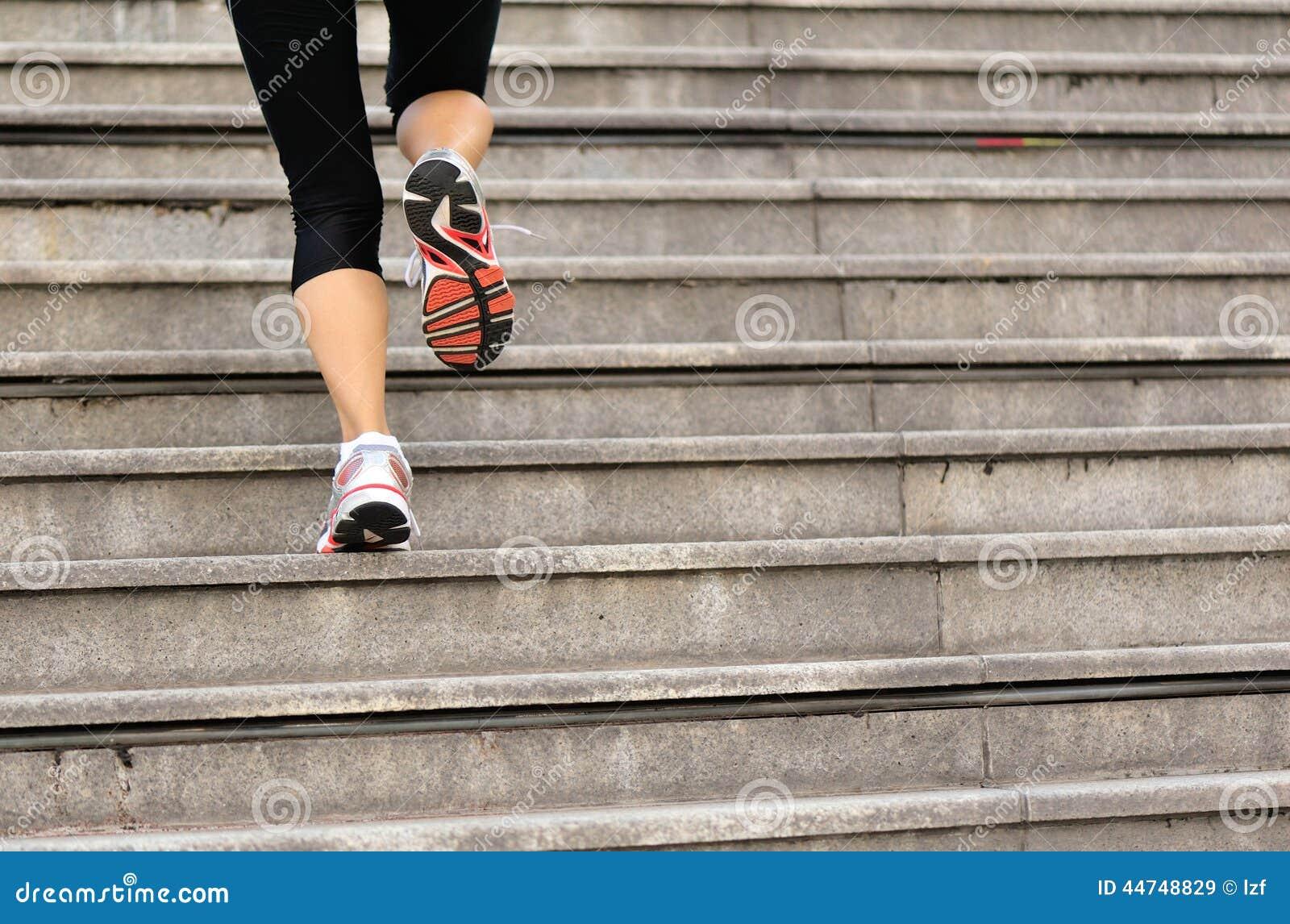 Frau, die oben auf Steintreppe läuft