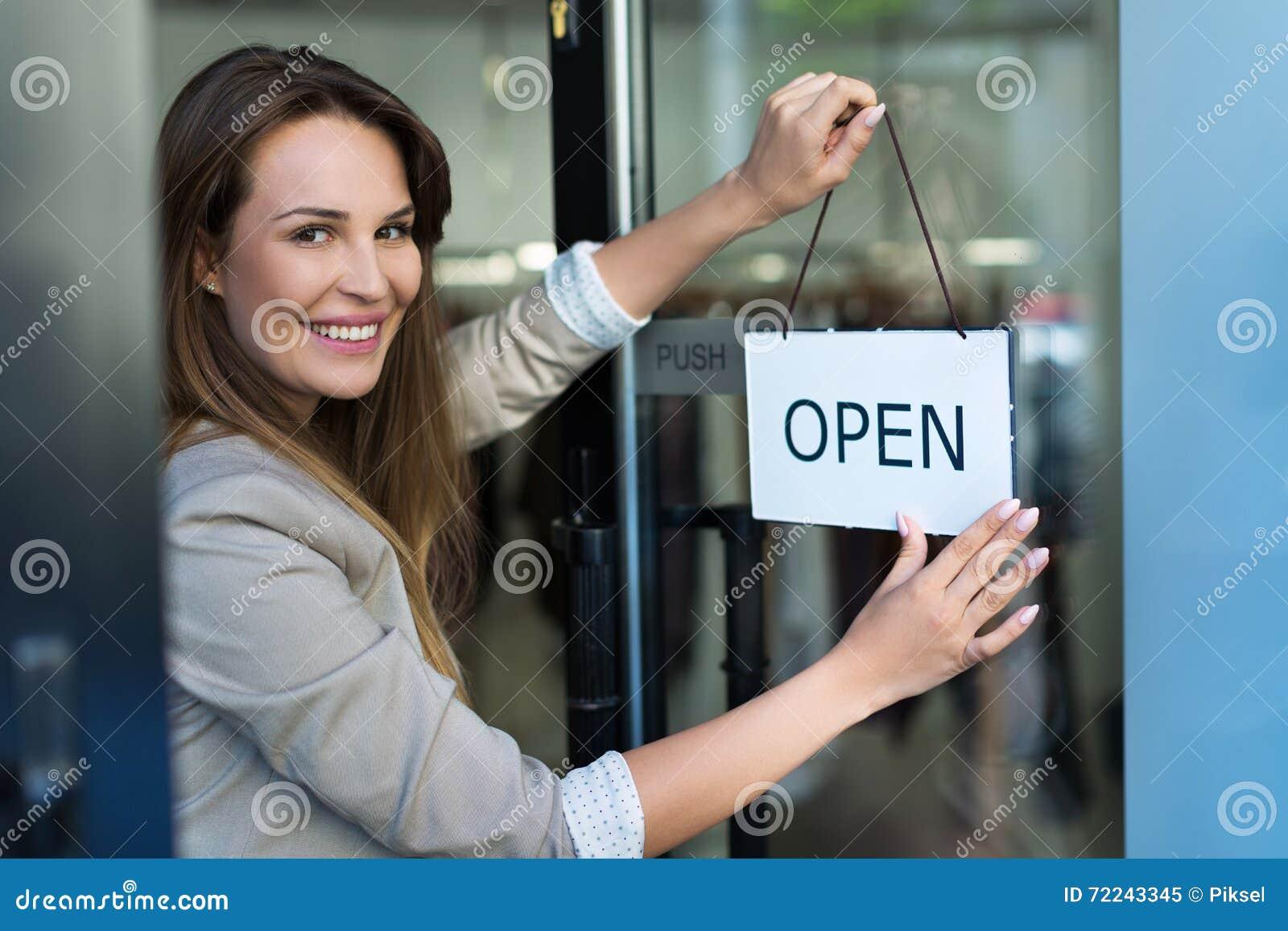 Frau, die offenes Zeichen auf Tür hängt