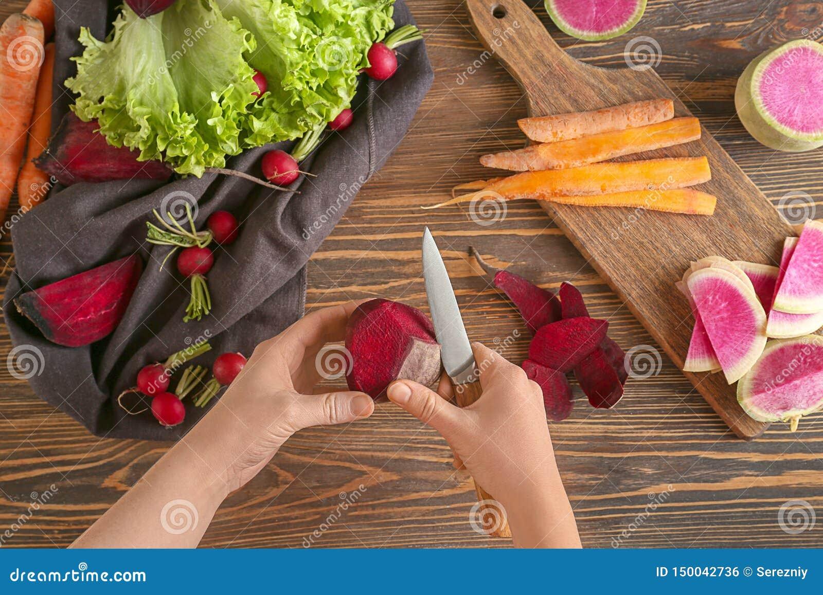 Frau, die reifer roter Rübe über Holztisch, Draufsicht abzieht