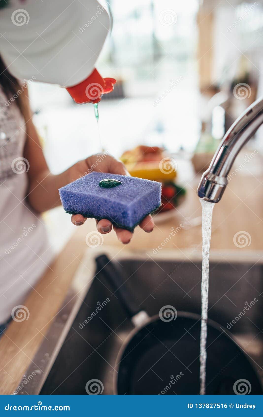 Frau, die Reiniger zu einem Schwamm setzt Händewaschenteller